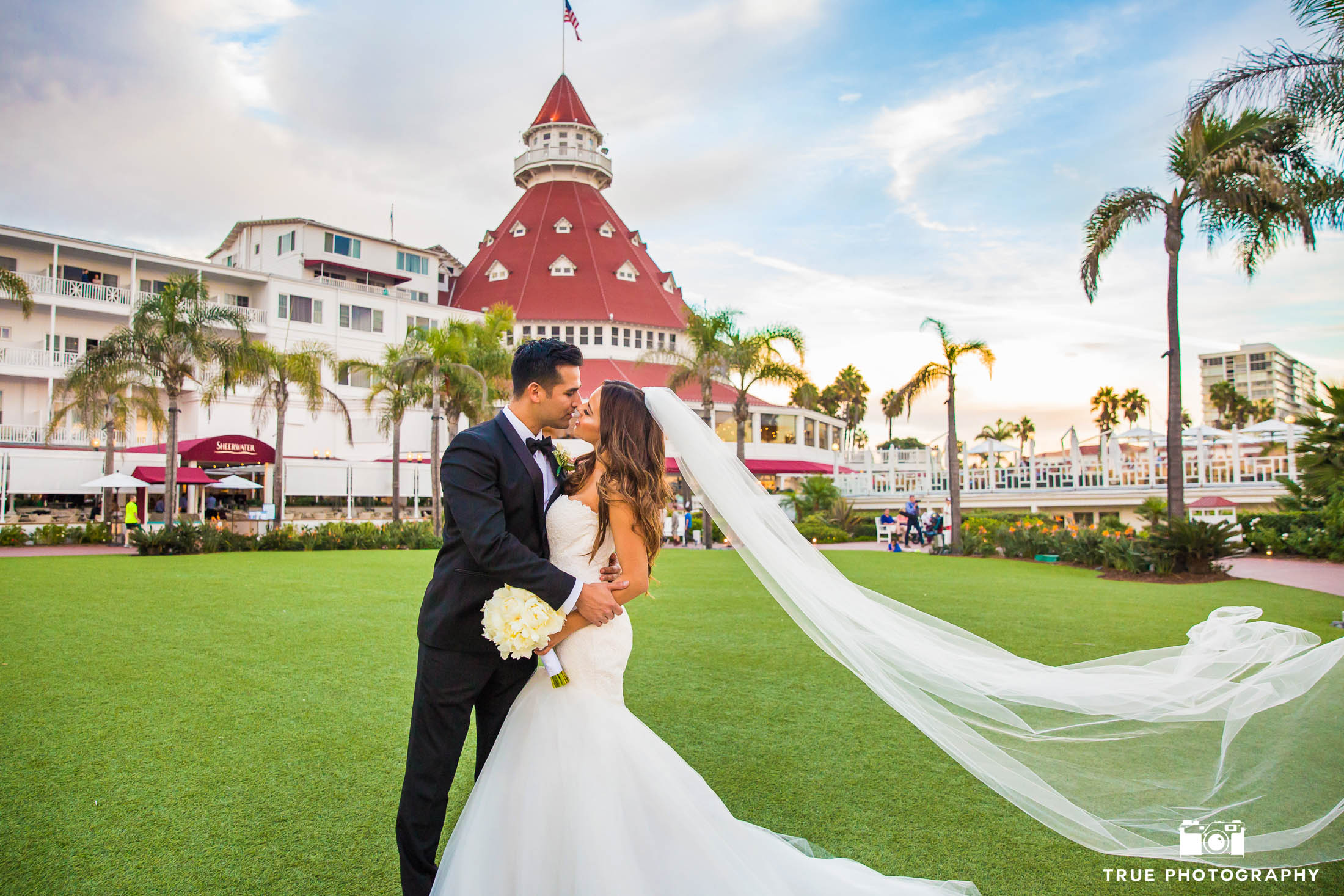 Groom dips Bride for kiss in front of Hotel Del Coronado