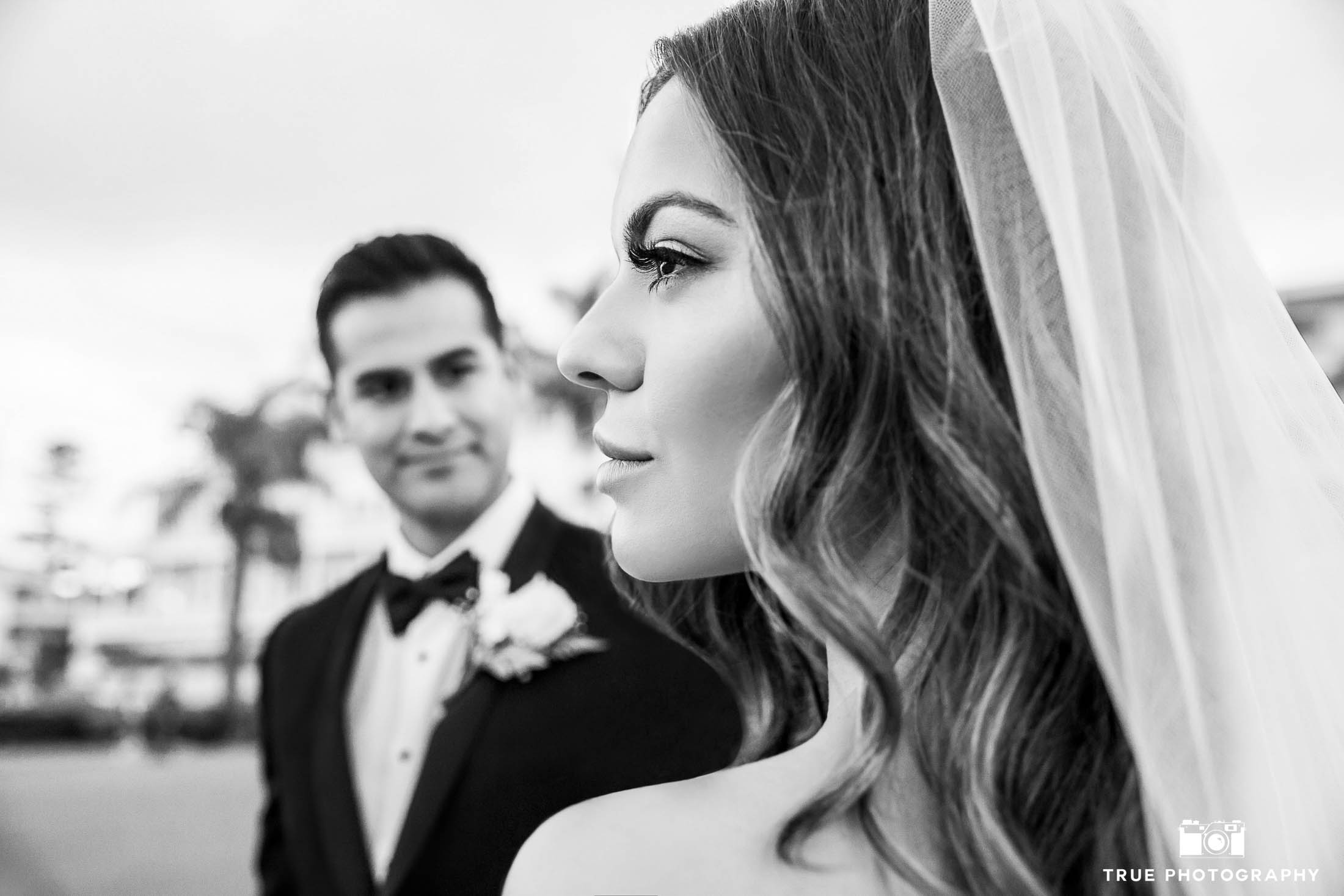 Side profile of Bride looking away as Groom looks at her from background