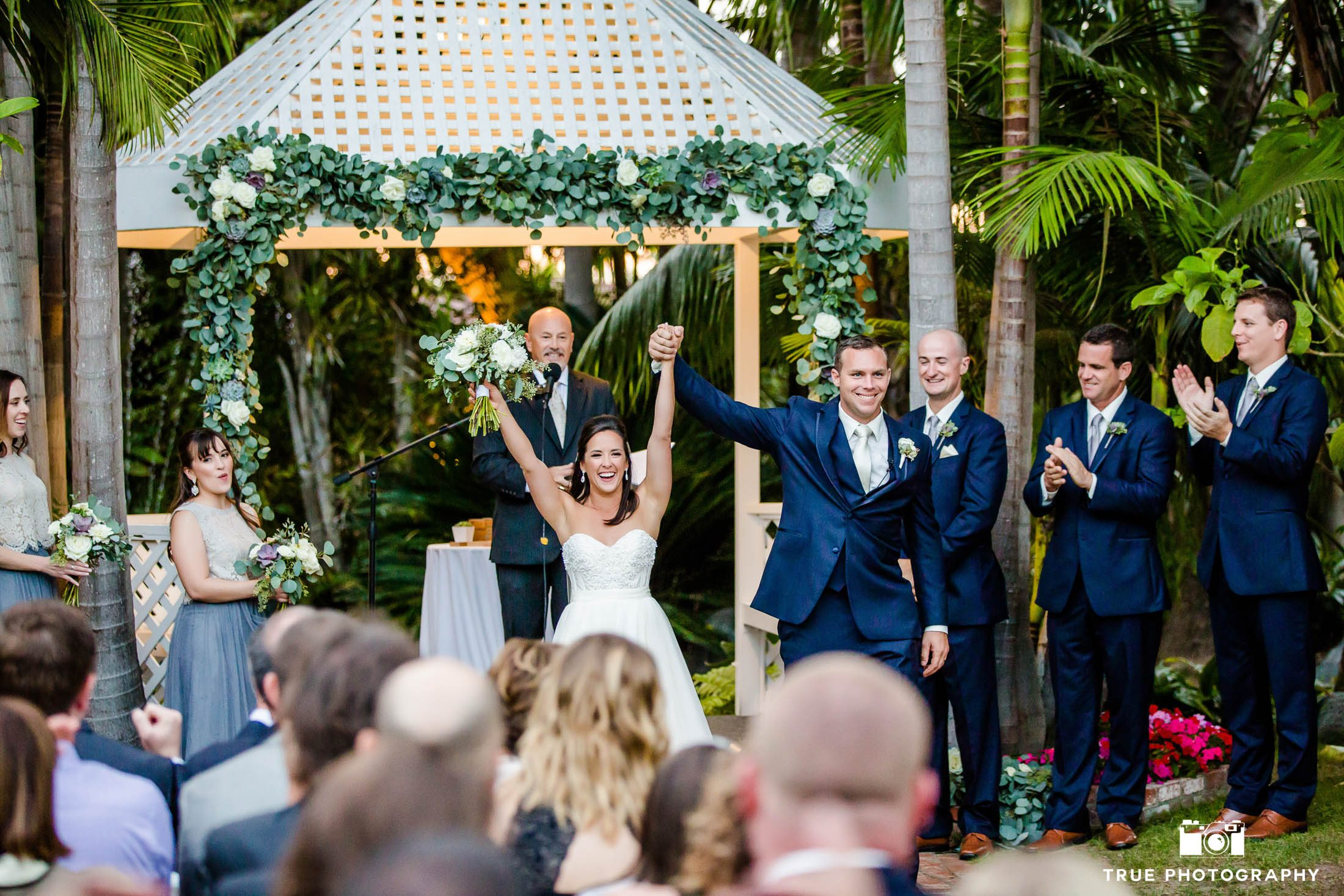 Bride and Groom cheer as they walk down aisle after wedding ceremony