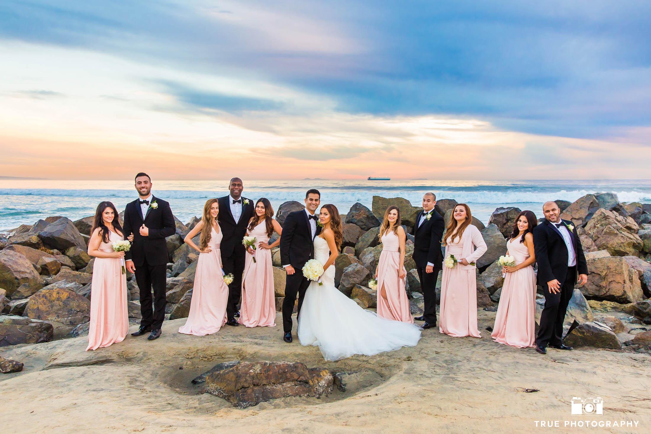 Bridal party with wedding couple on rocks at Coronado Beach