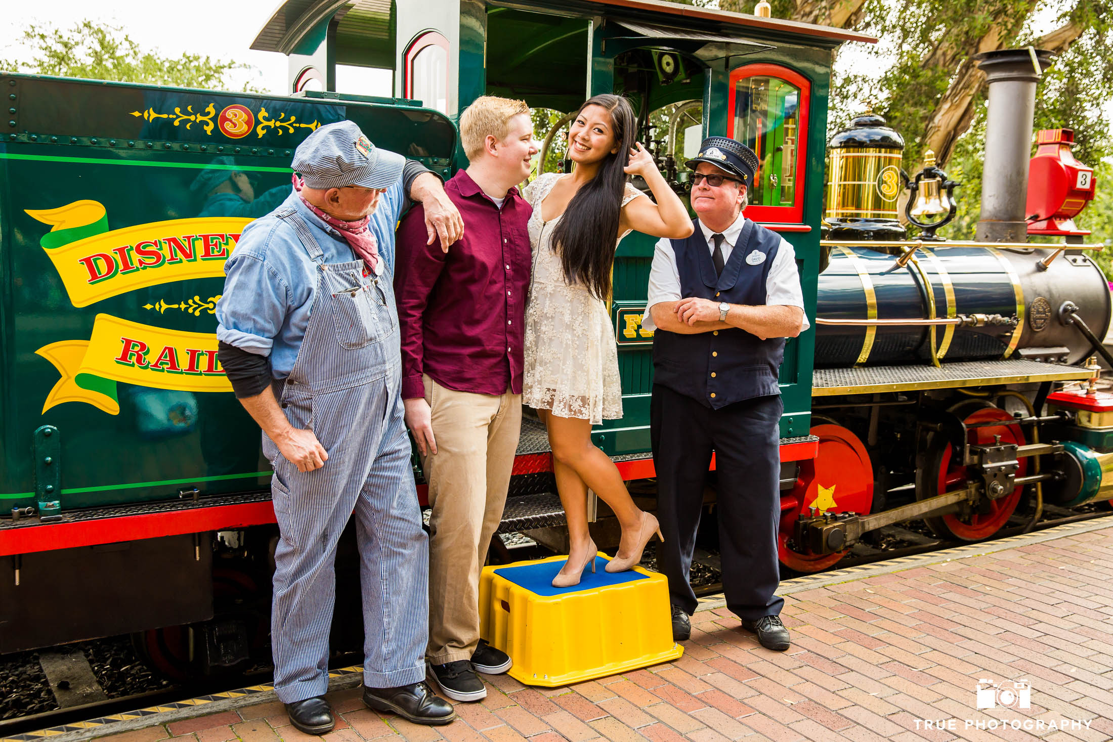 Engaged couple stand by train with conductors at Disneyland
