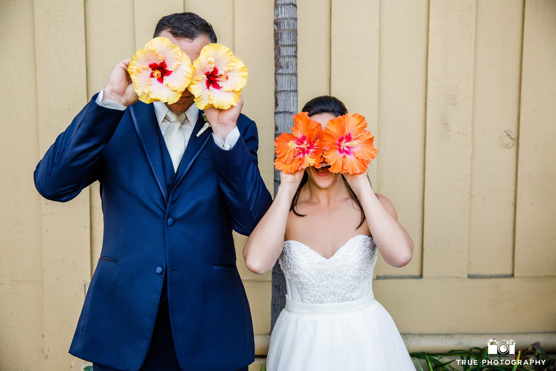 Funny Bride and Groom hold tropical flowers in front of faces
