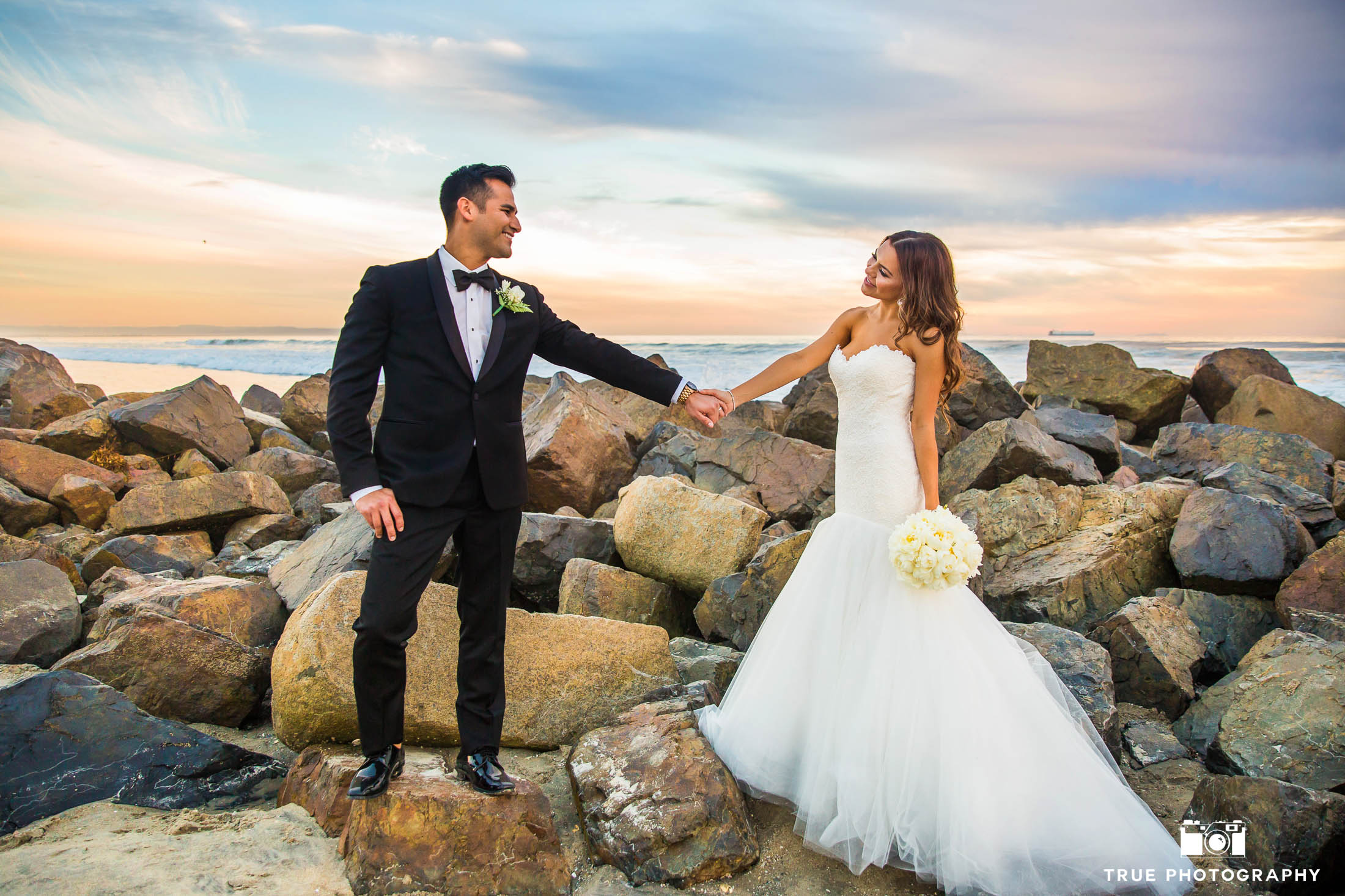 Bride and Groom hold hands on rocks at beach