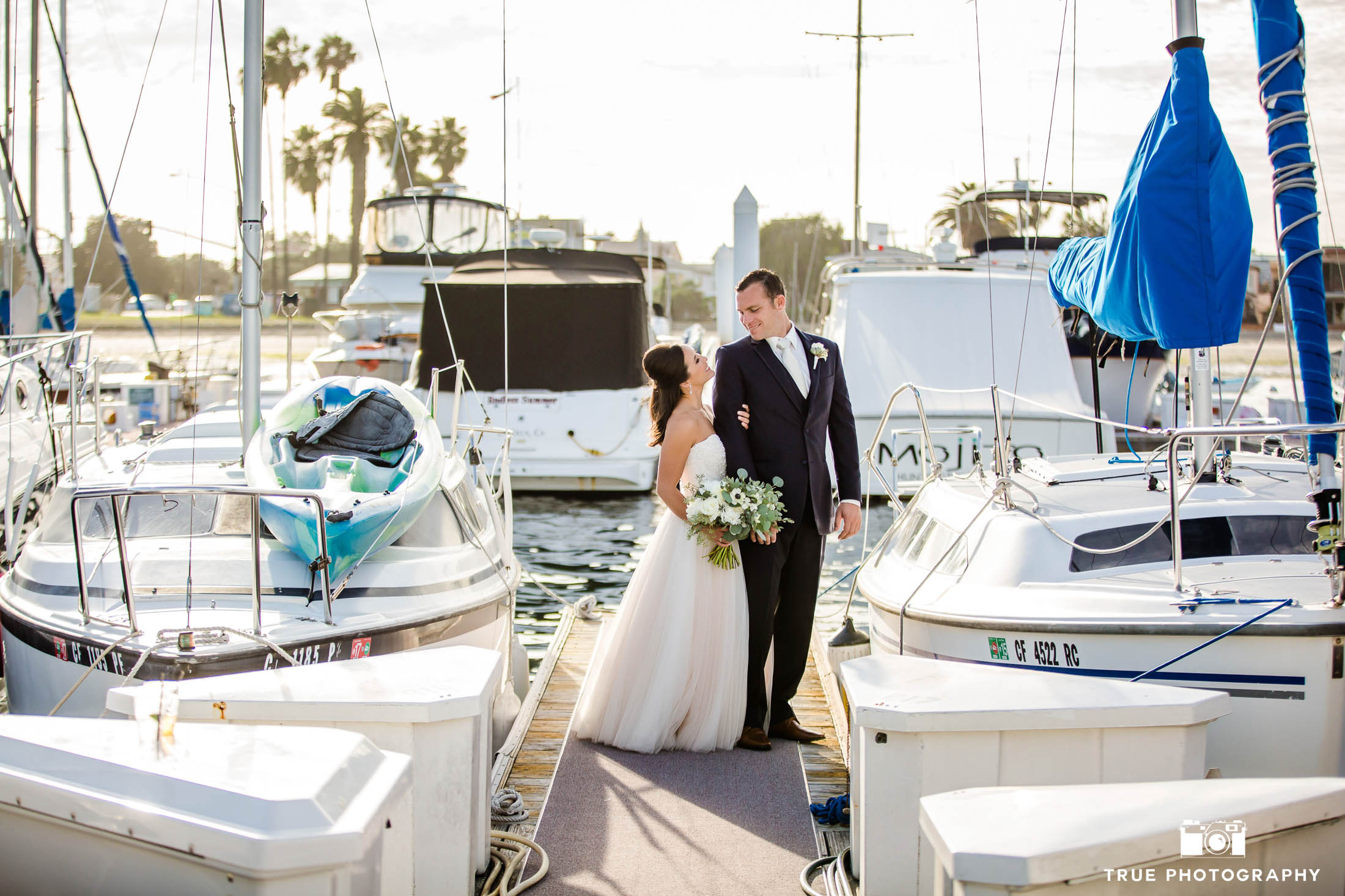 Bride and Groom look at one another in marina