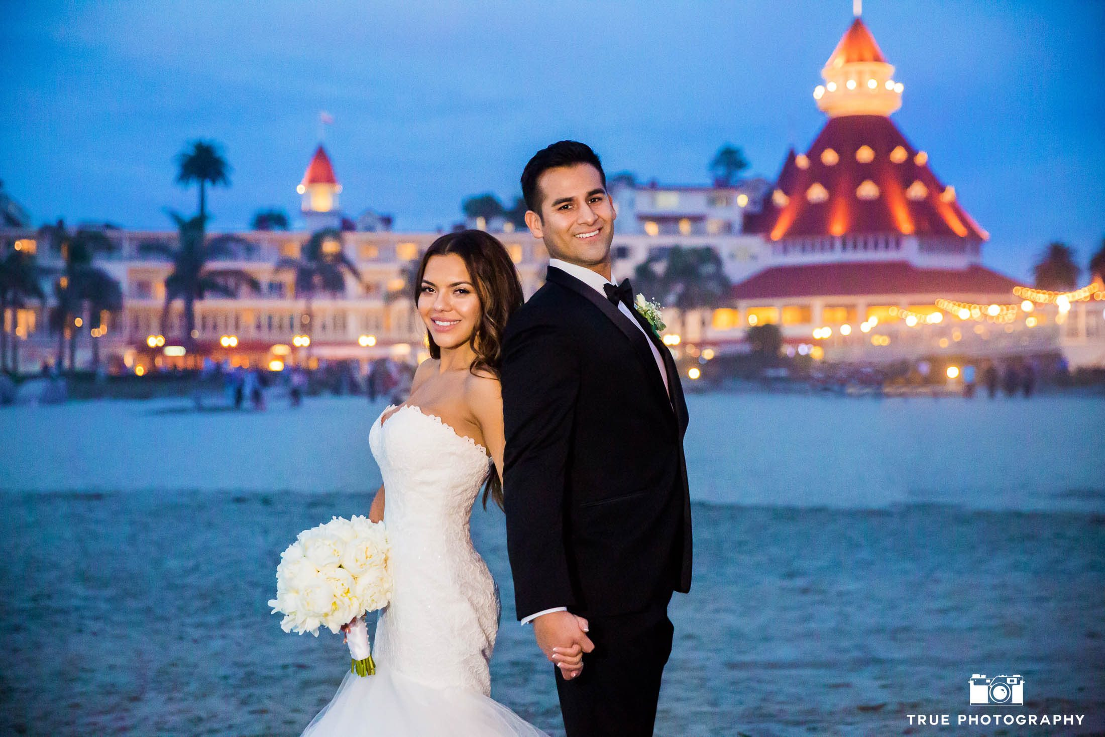 Bride and Groom hold hands in front of Hotel Del Coronado
