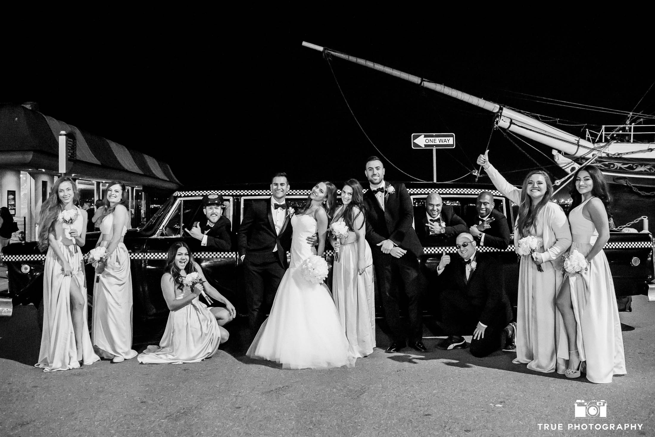 Bridal Party cheers in front of vintage taxi