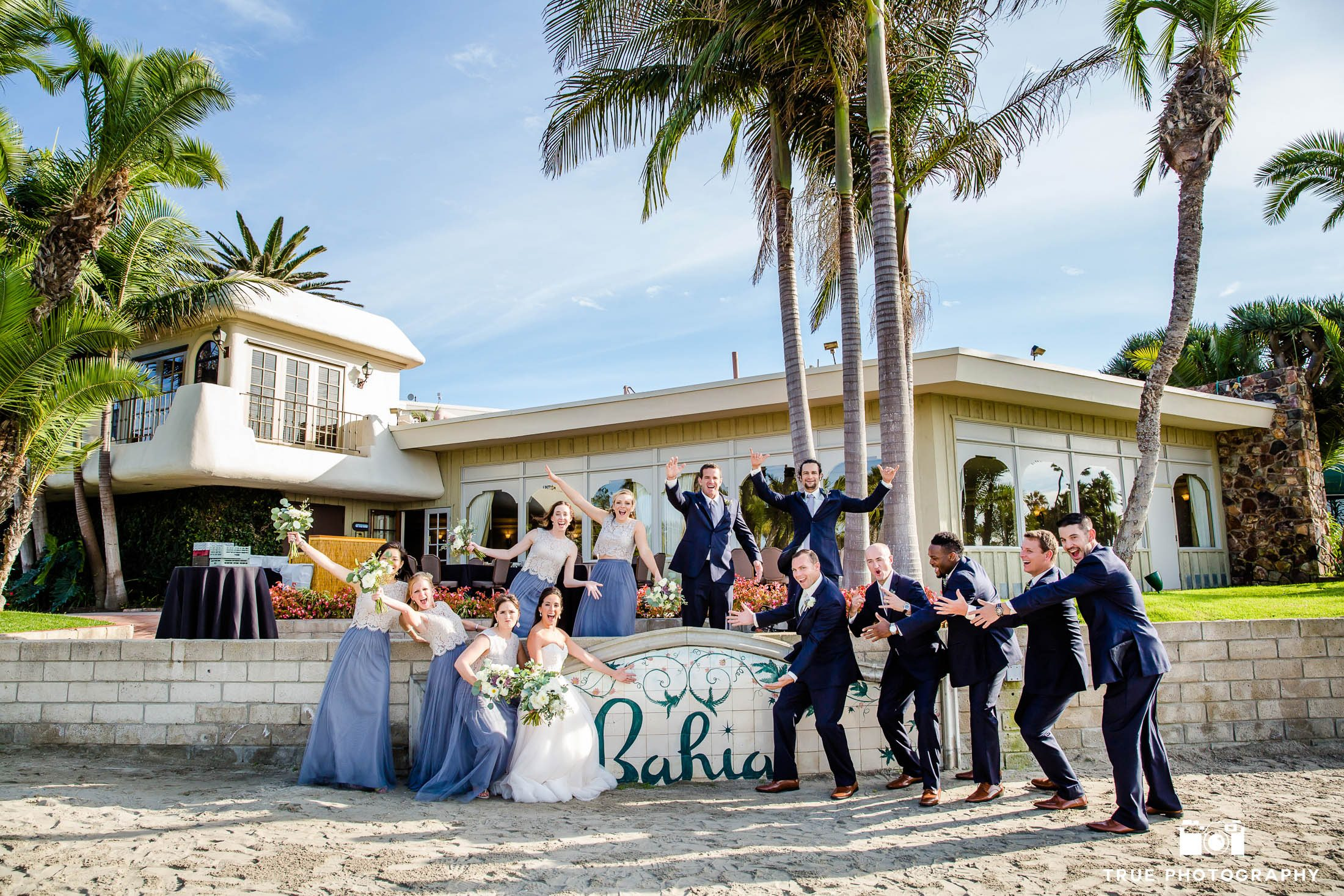 Wedding bridal party cheer in front of sign at Bahia Resort