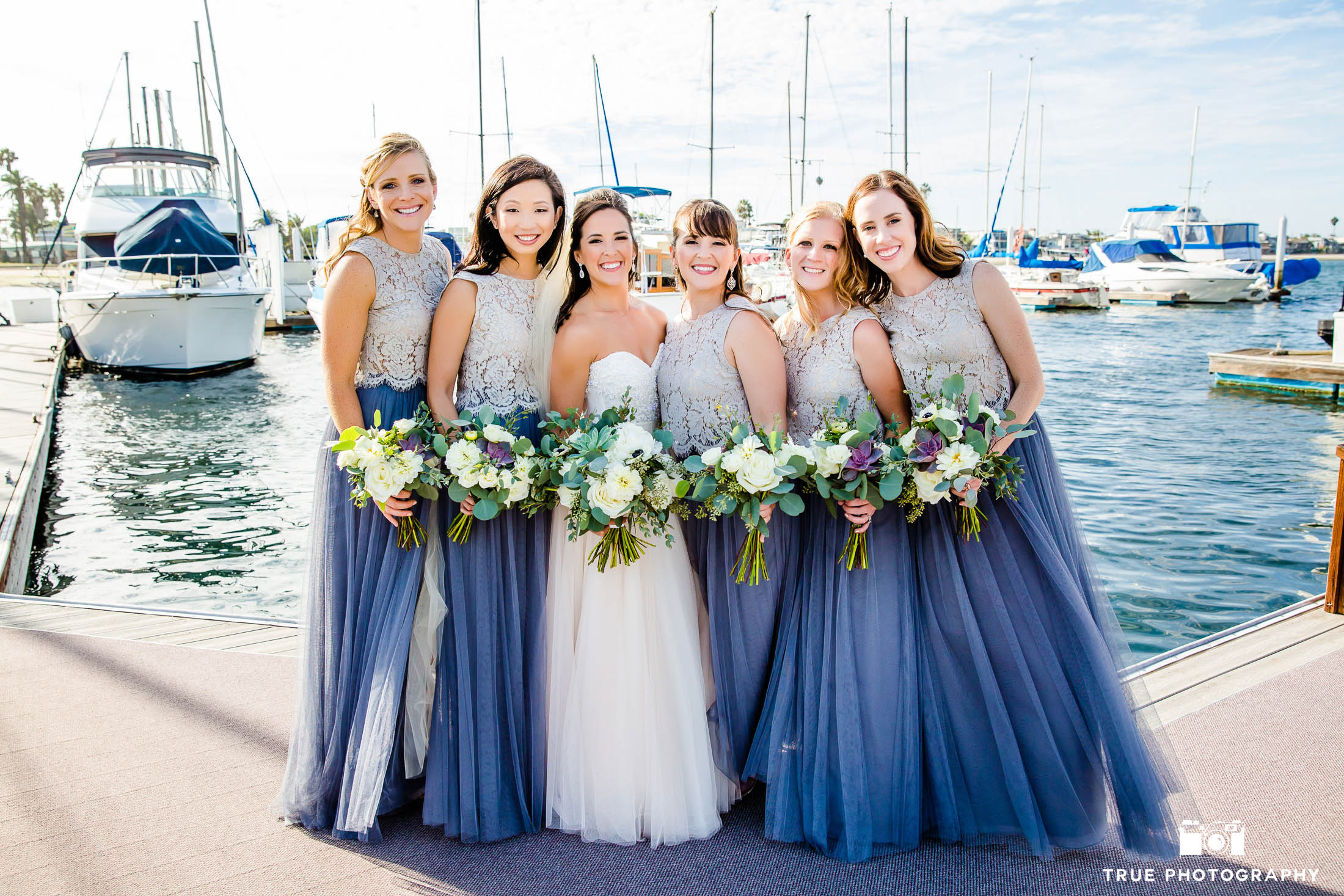 Bride with bridesmaids in 2-piece dresses at marina