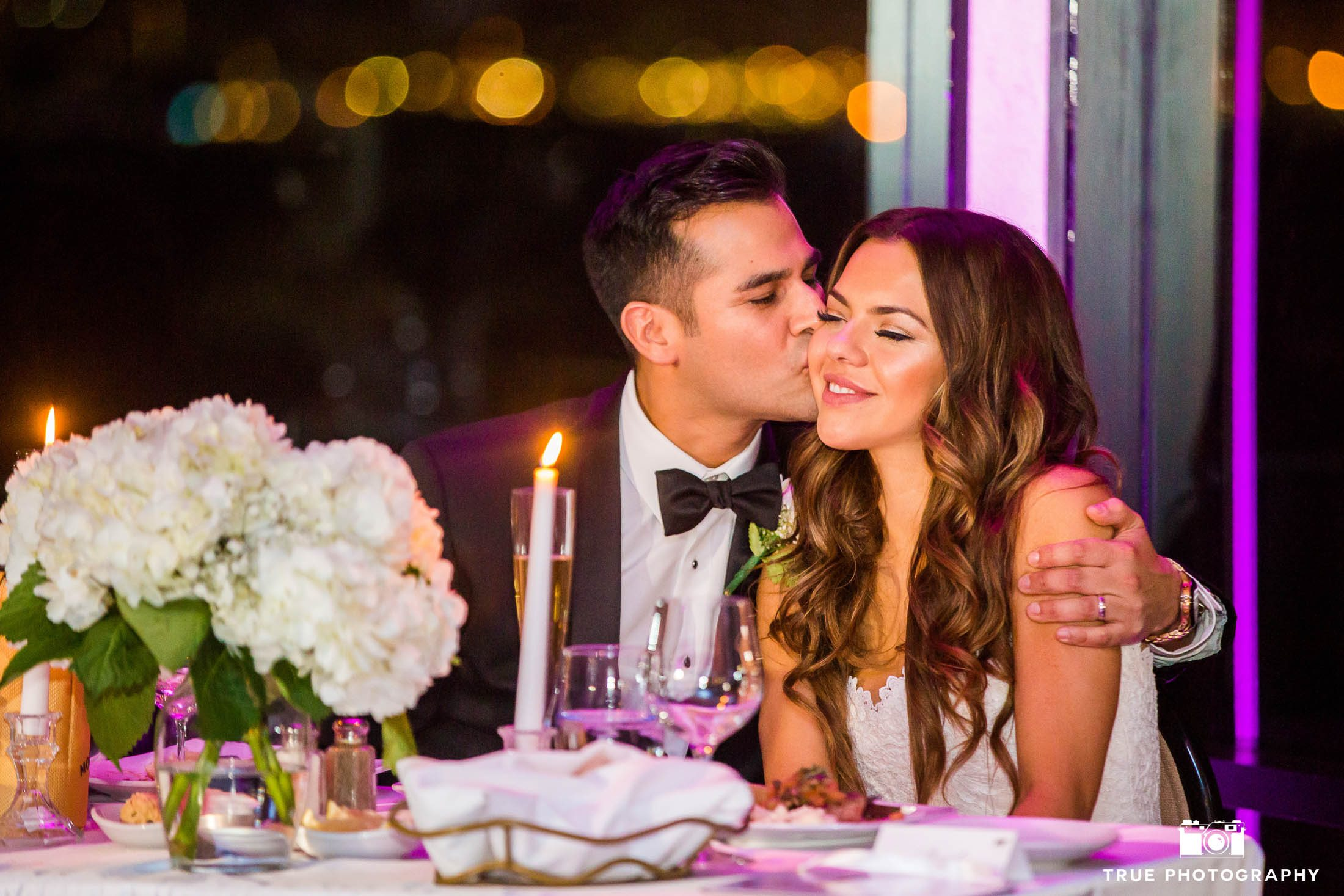 Groom kisses Bride at Sweetheart Table