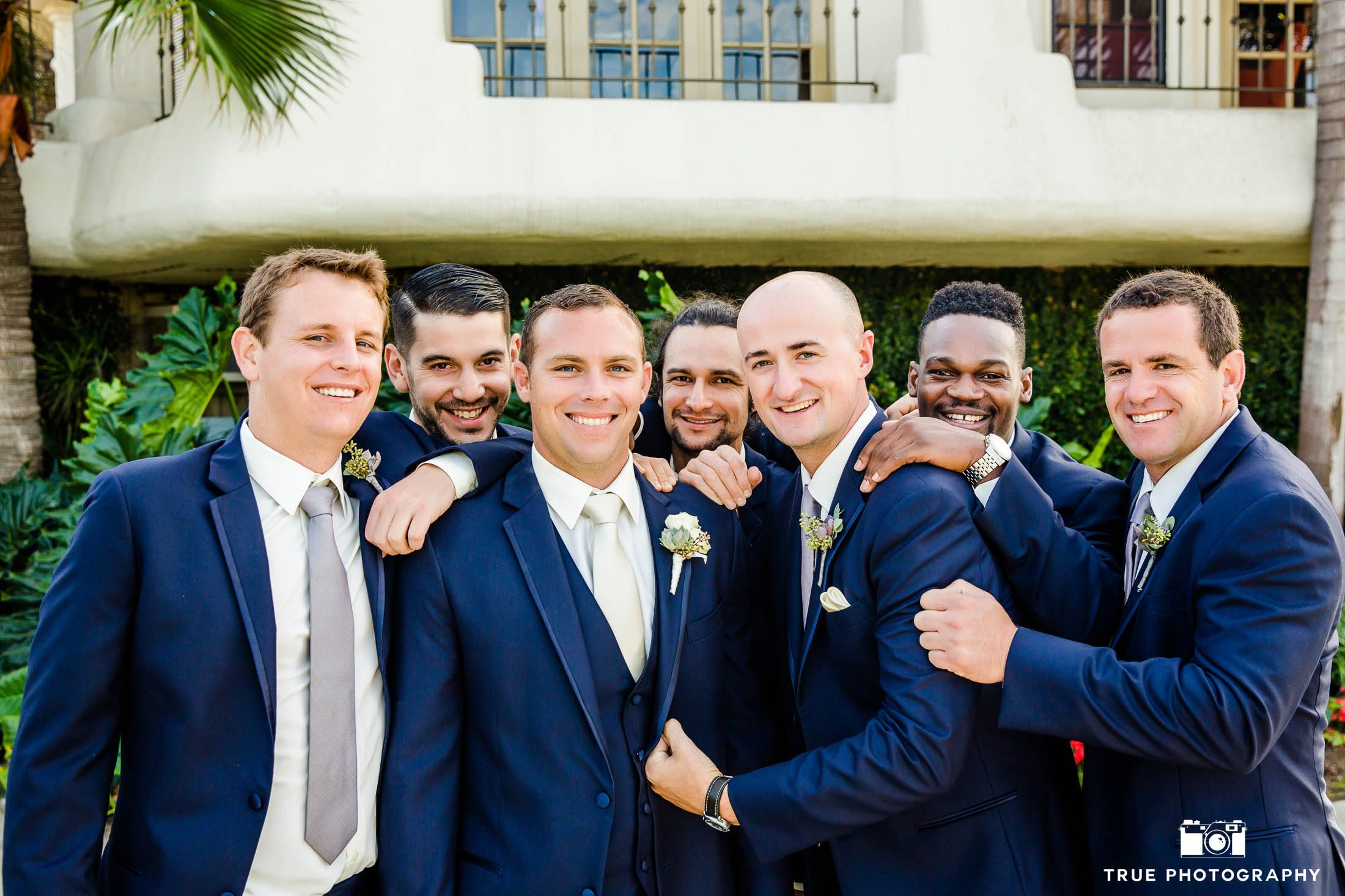 Groomsmen hug groom for funny photo