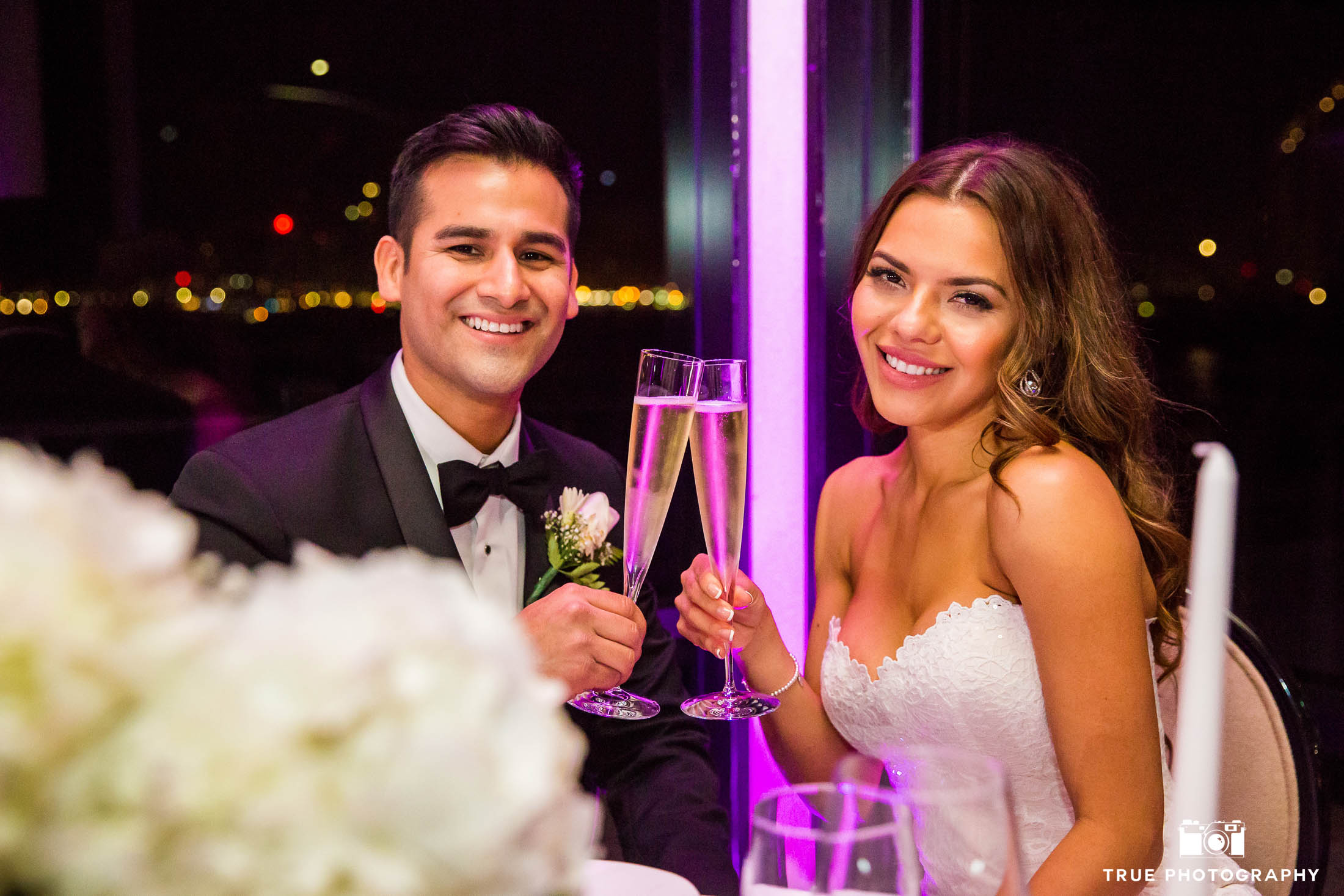 Bride and Groom smile at camera for champagne toast during reception