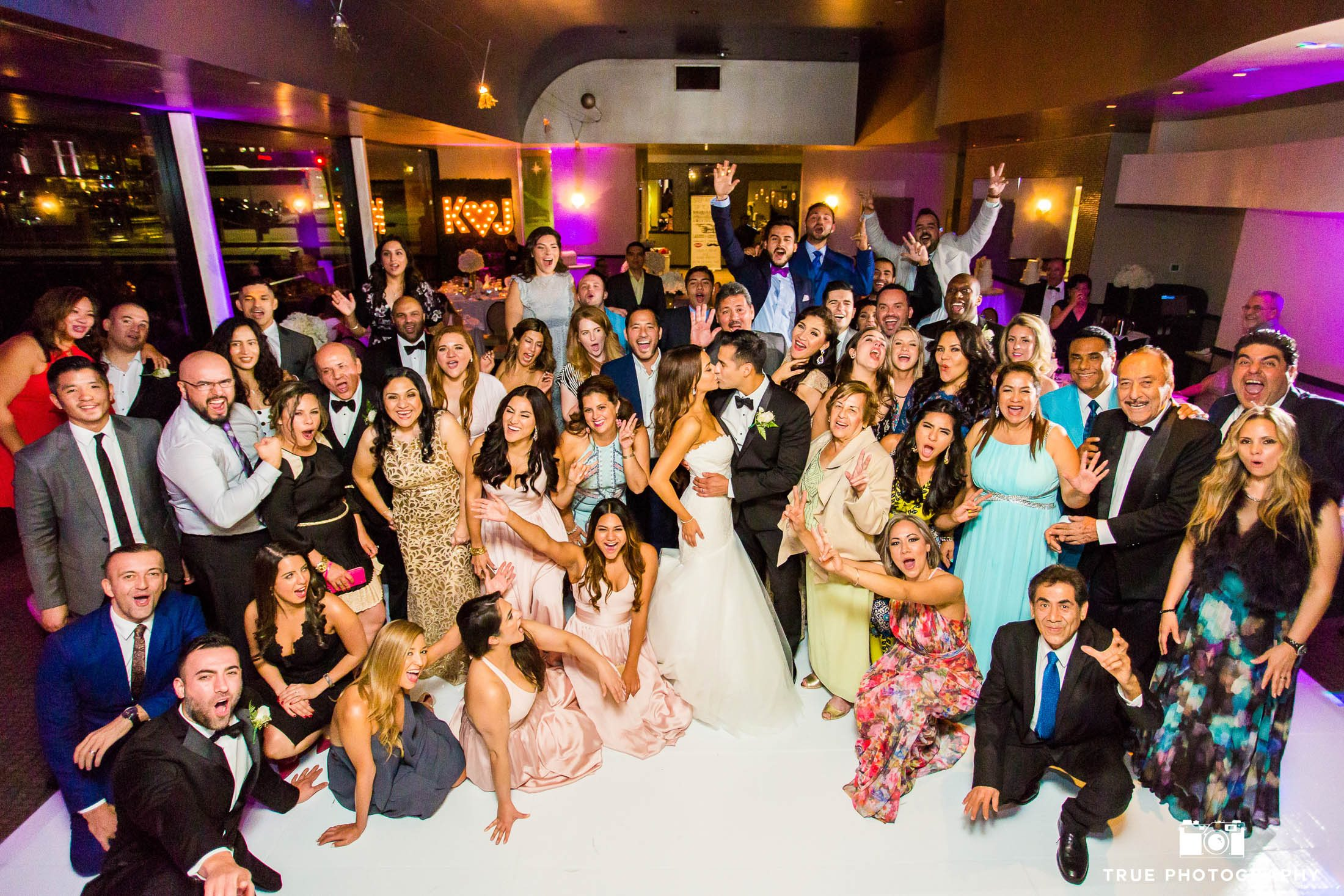 Guests join wedding couple on dance floor for group photo