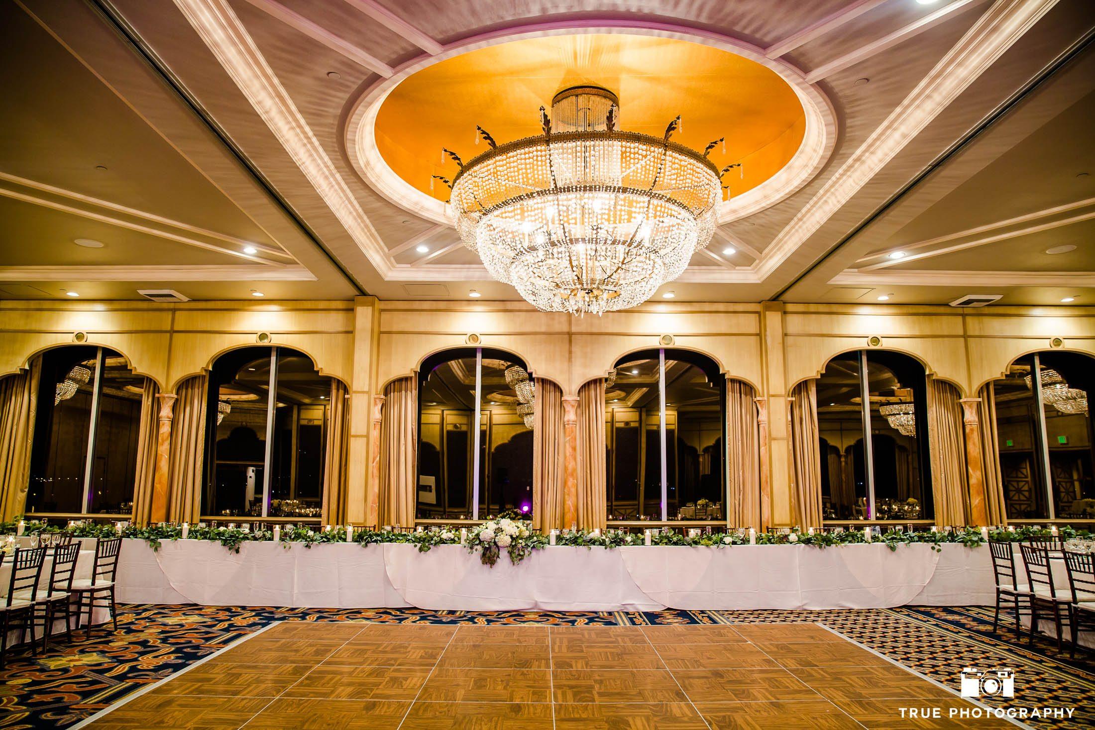 Grand chandelier below sweetheart table at reception in Bahia Resort