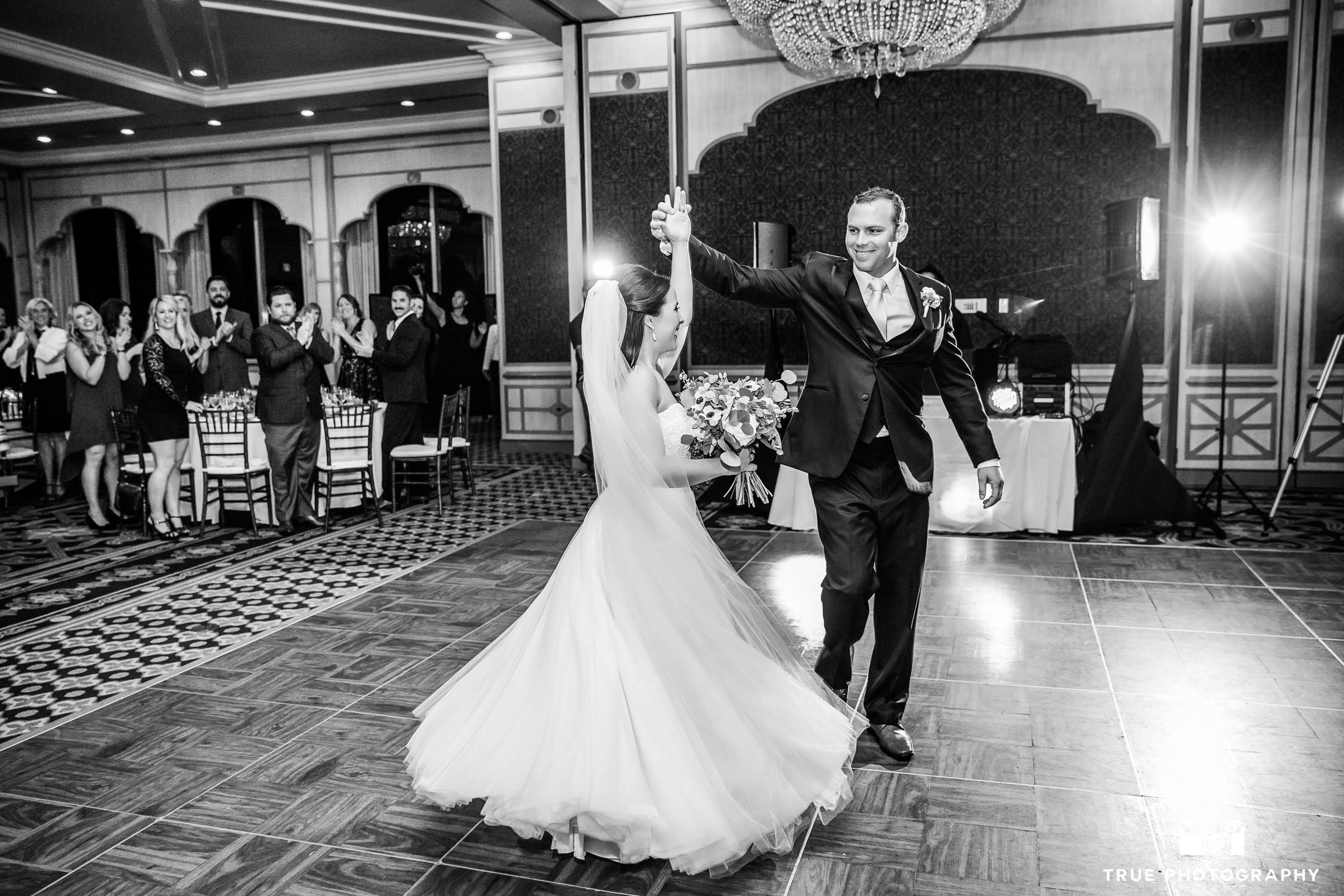 Groom twirls Bride during couple's first dance at reception