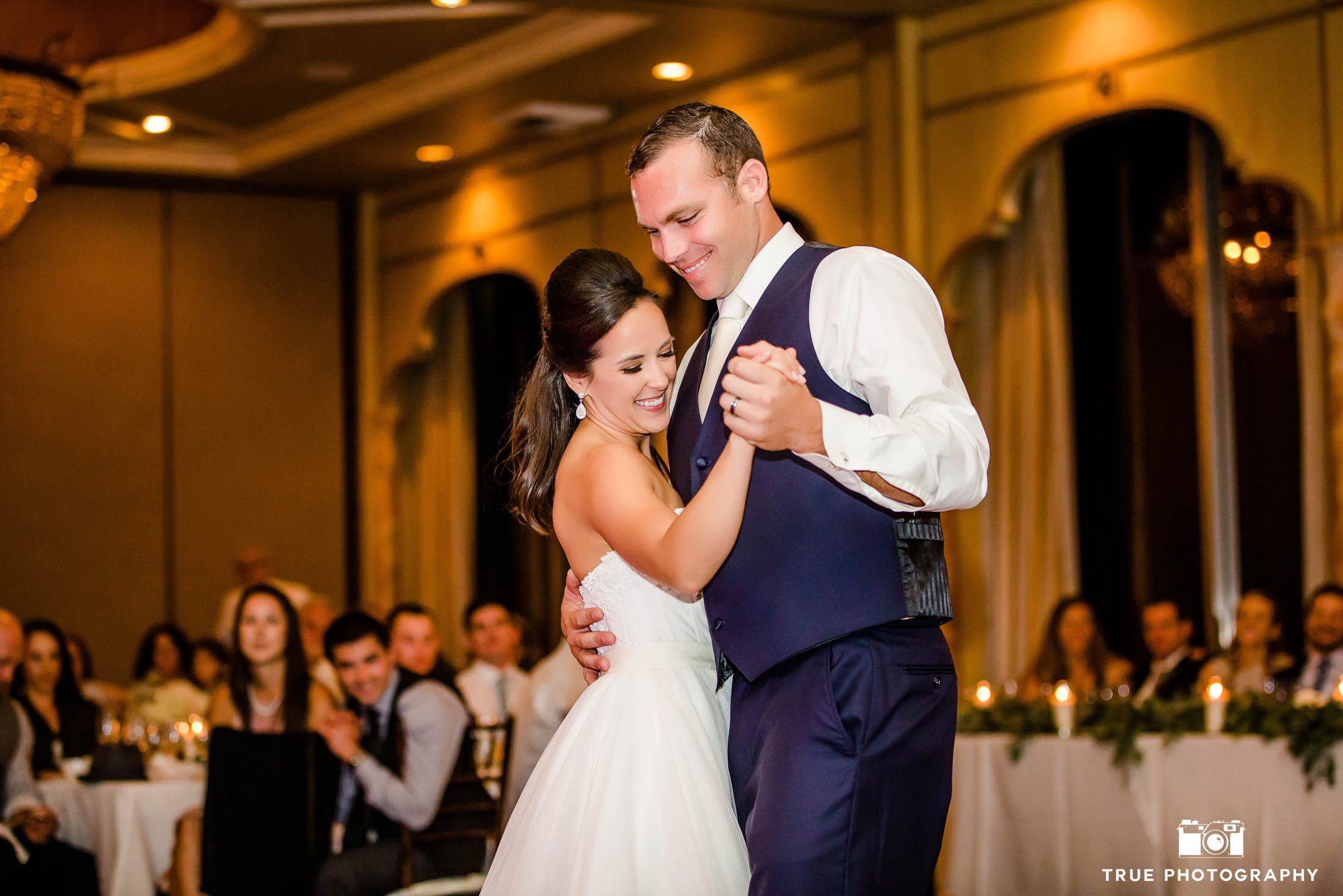 Grooms embraces Bride as they smile during First Dance