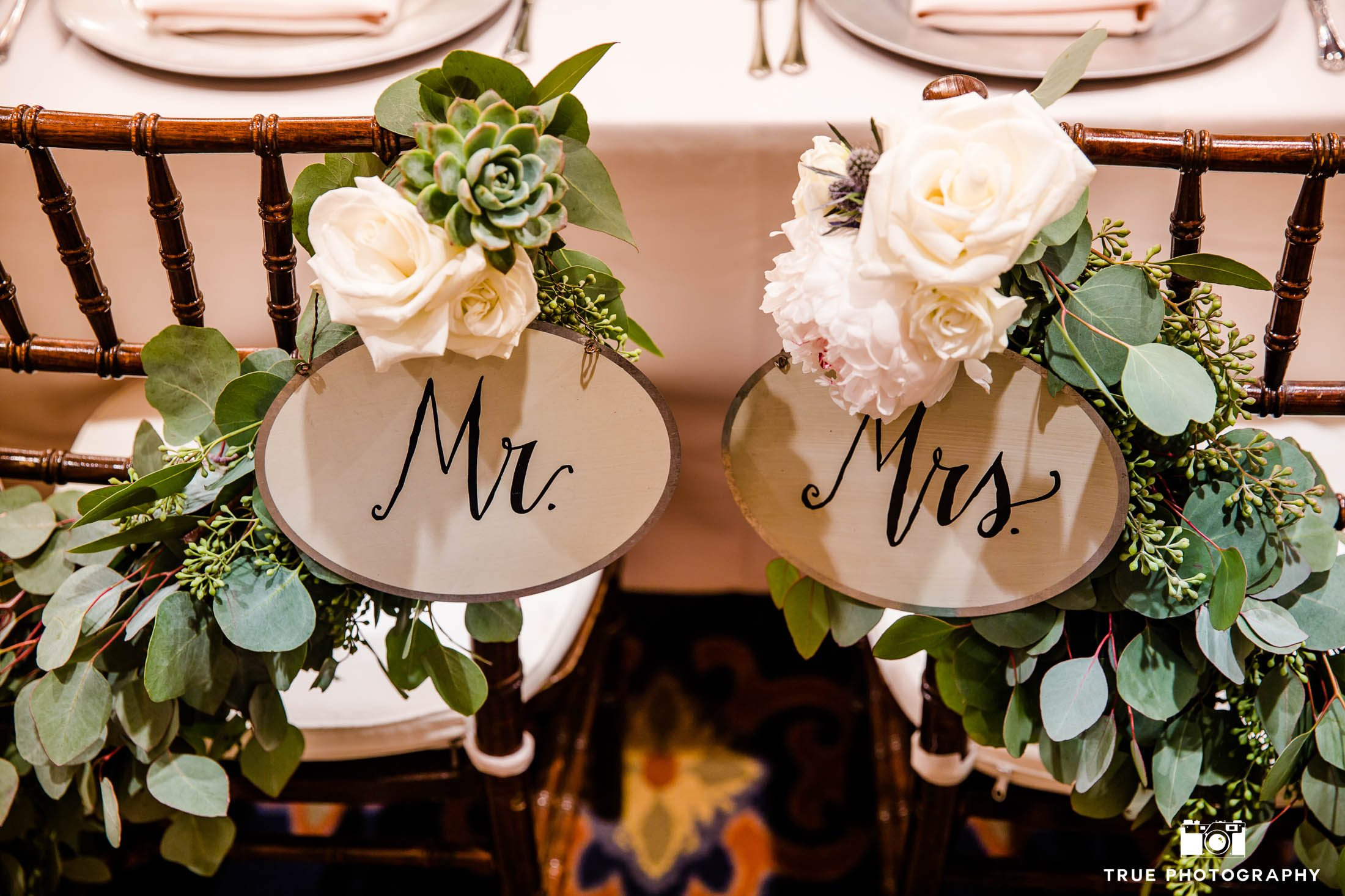 Mr. and Mrs. signs with flowers decorate sweetheart table chair