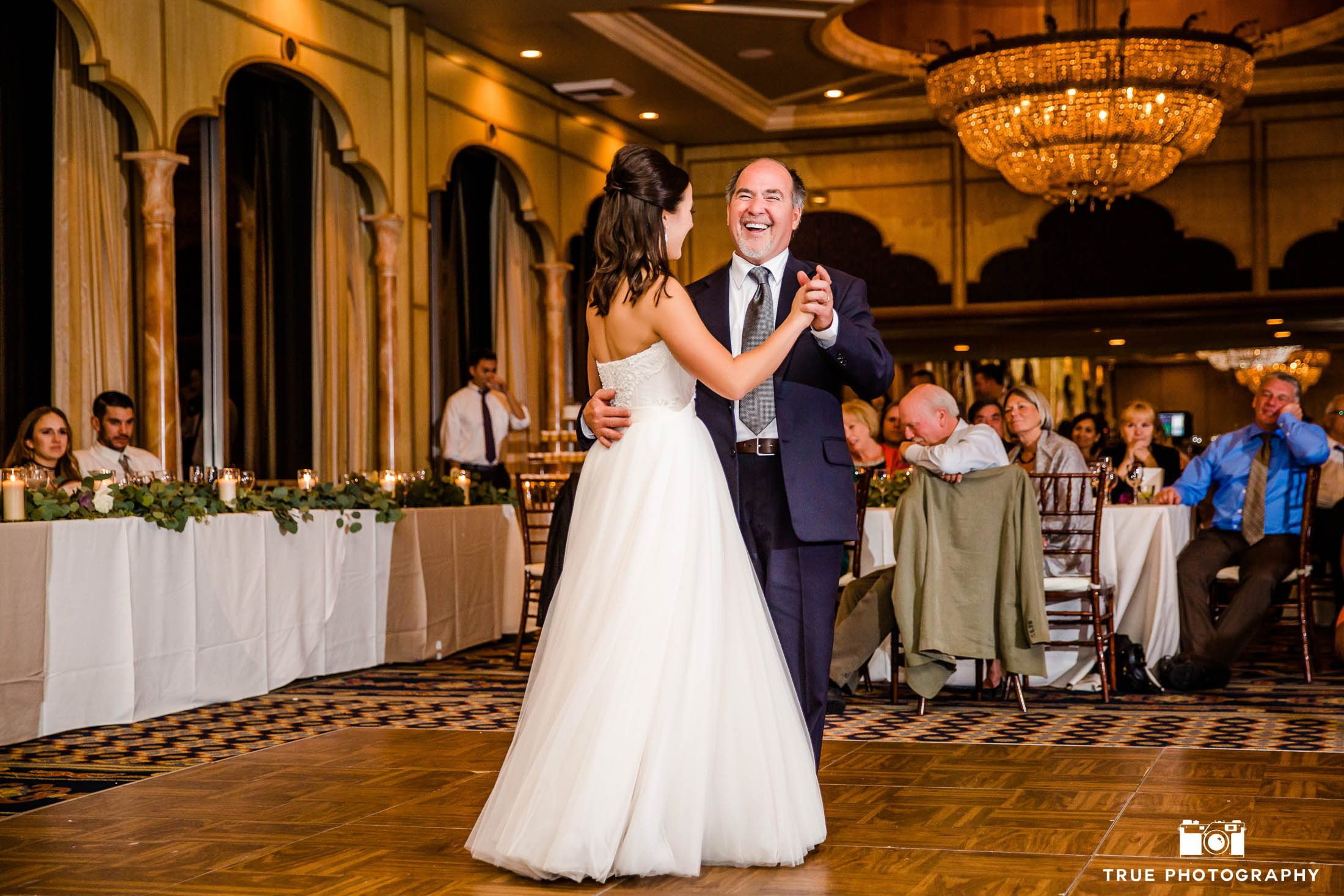 Father smiles while dancing during father and daughter dance at wedding reception