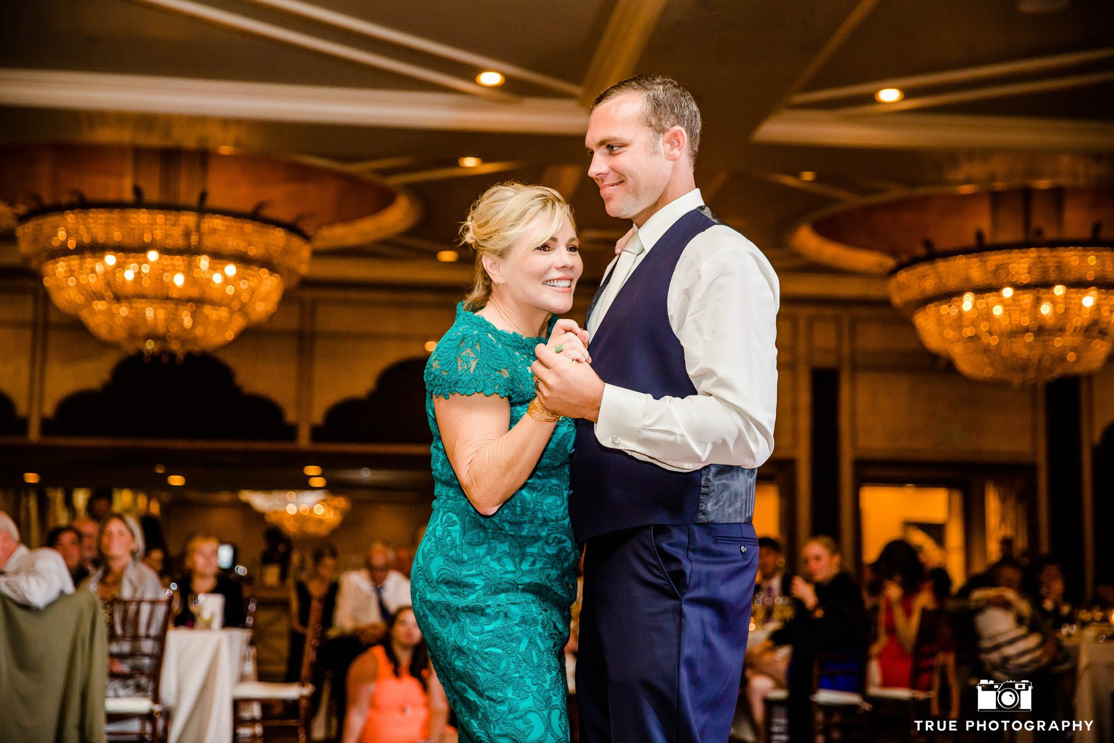 Groom and Mother smile during Mother and Son dance at wedding reception