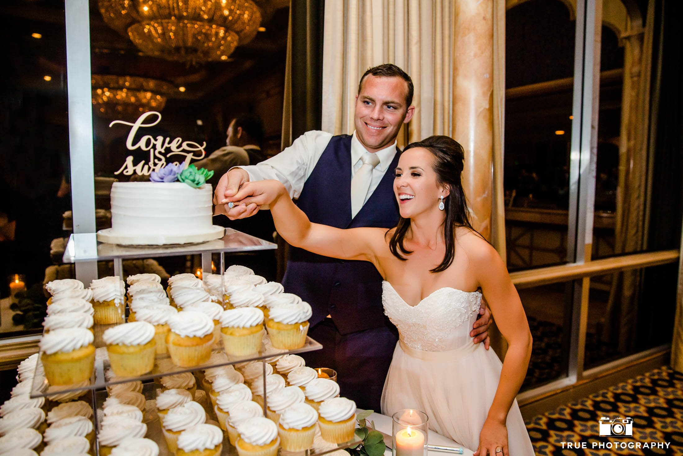 Bride and Groom hold hands and cut cake together during reception in Mission Ballroom at Bahia Resort