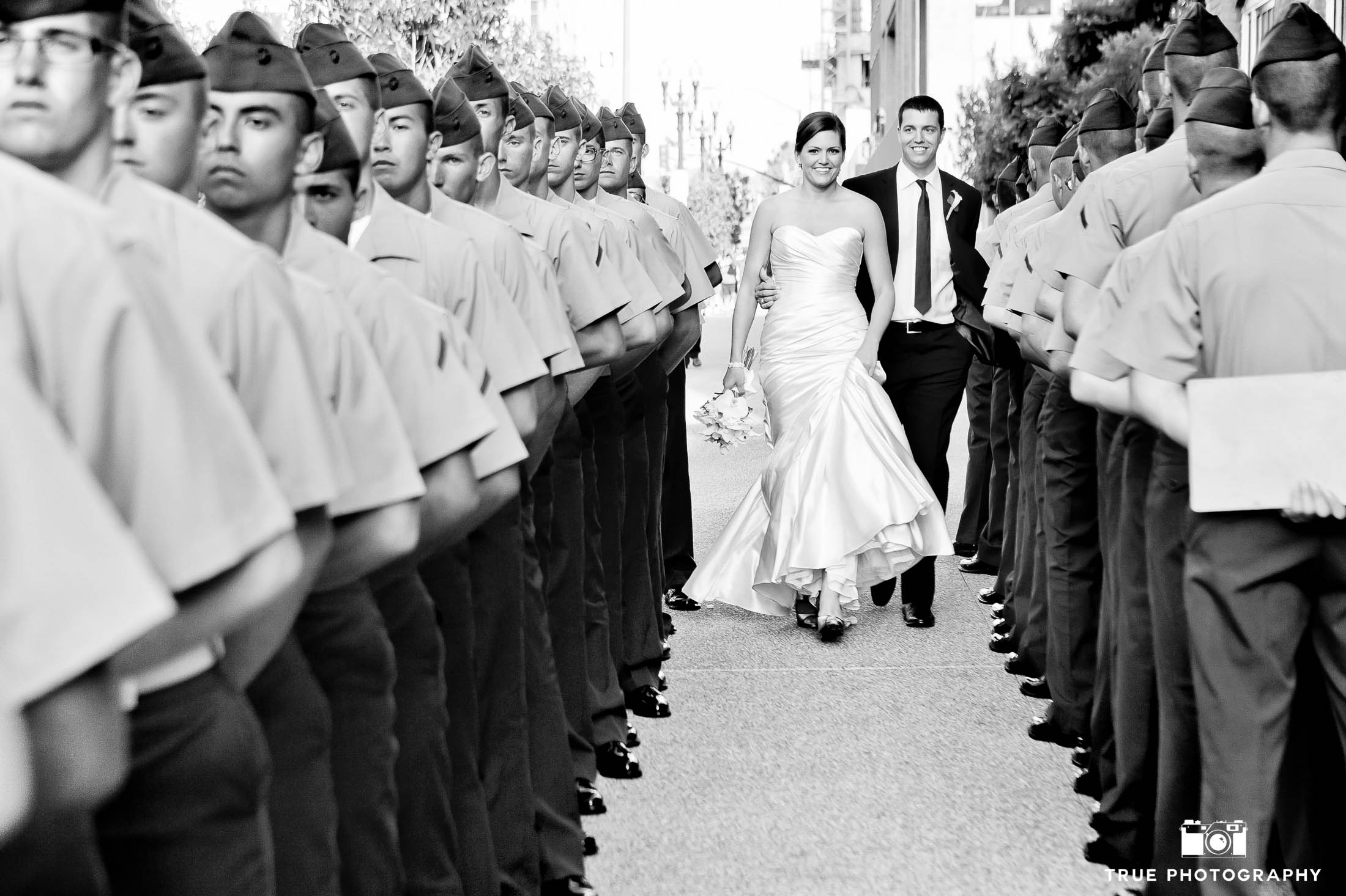 Bride and Groom smile and walk through row of armed service military men