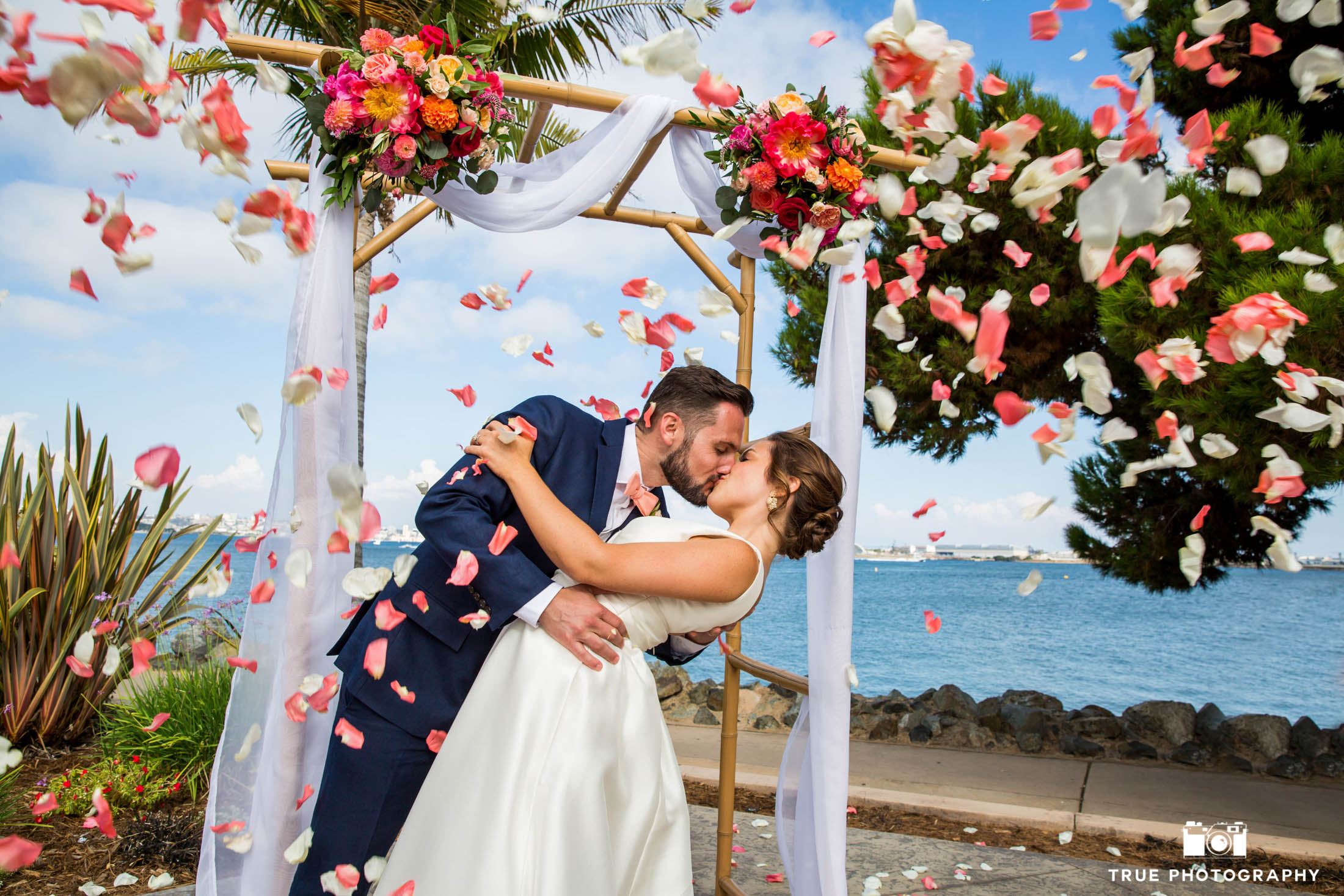 Bride and Groom Kiss under and arbor with flower petals