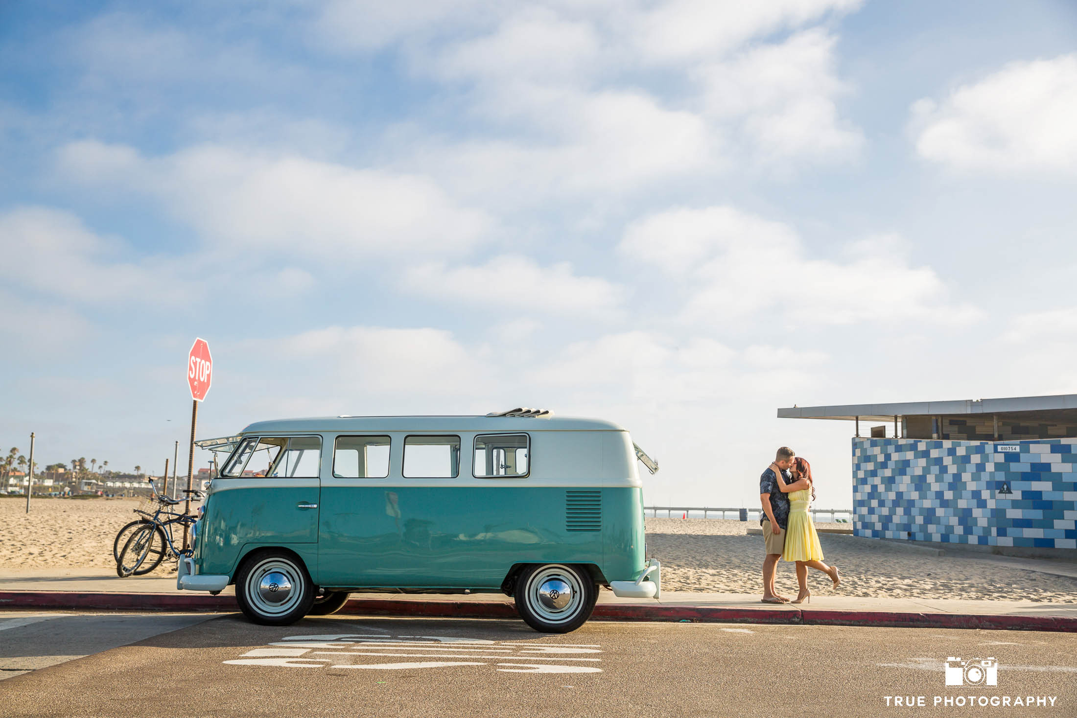 Engaged couple embrace and kiss next to vintage Volkswagen Bus at beach