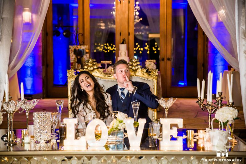 Bridal couple laugh during reception toast