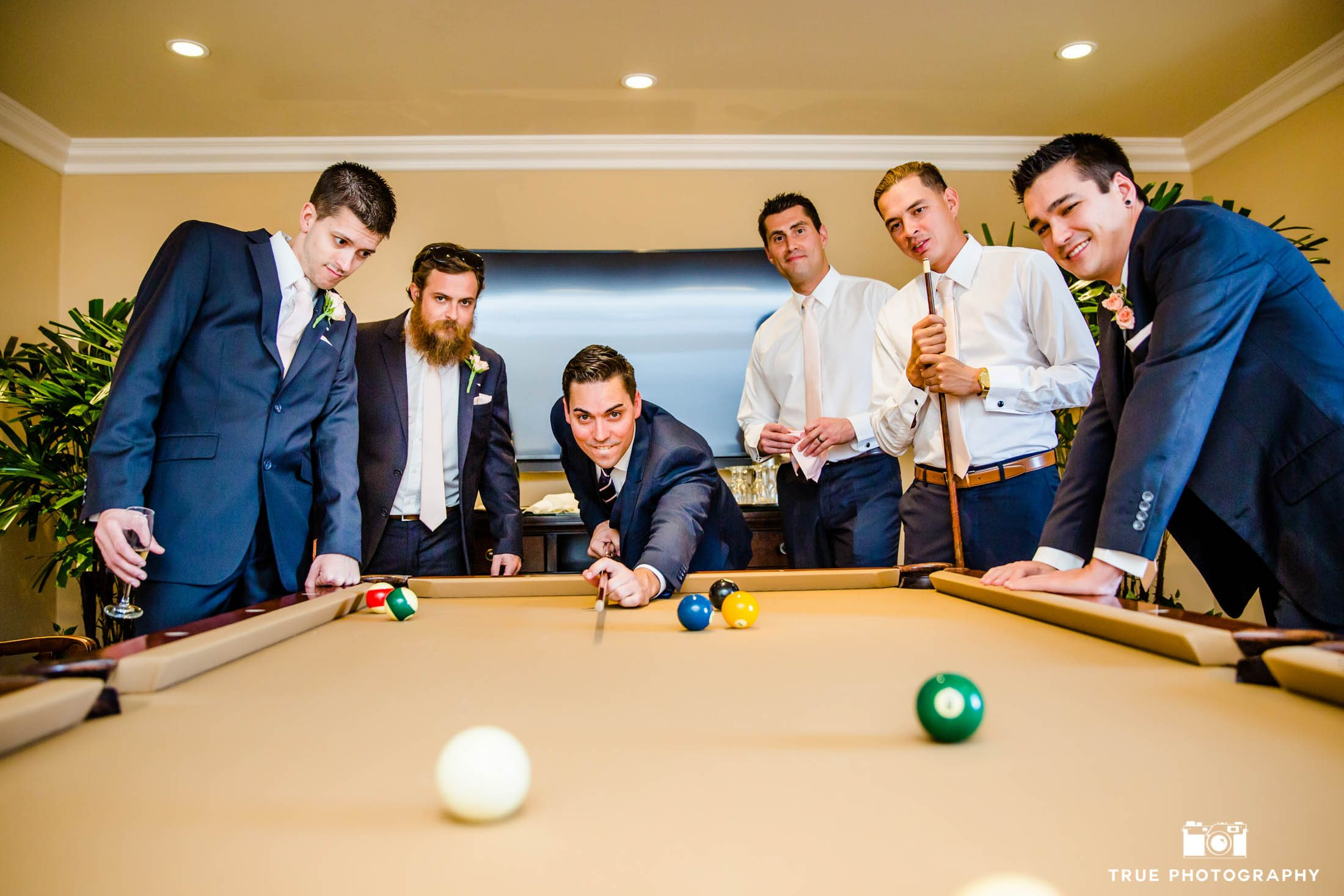 Groom with his groomsmen take some time to play some pool.