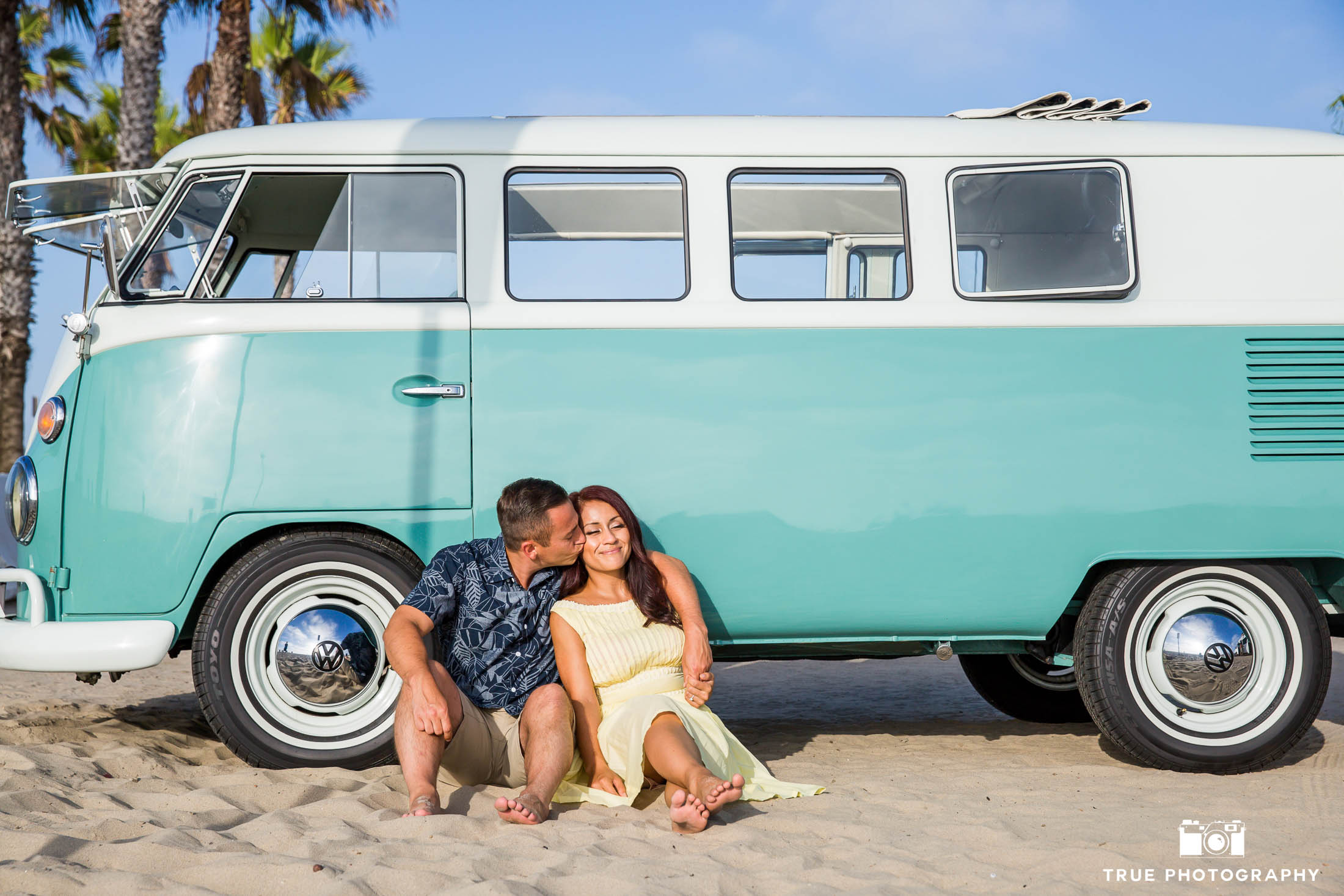 Engaged couple sit against vintage Volkswagen bus on sandy beach during engagement session