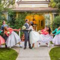 50's style dressed wedding party playing tug of war