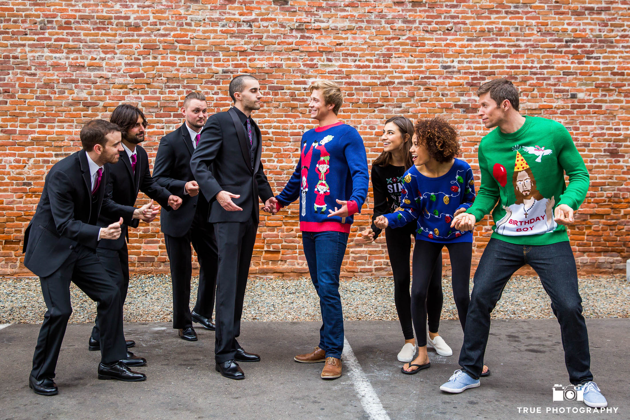 Groom and groomsmen snapping fingers in front of brick wall with Tipsy Elves in ugly christmas sweaters