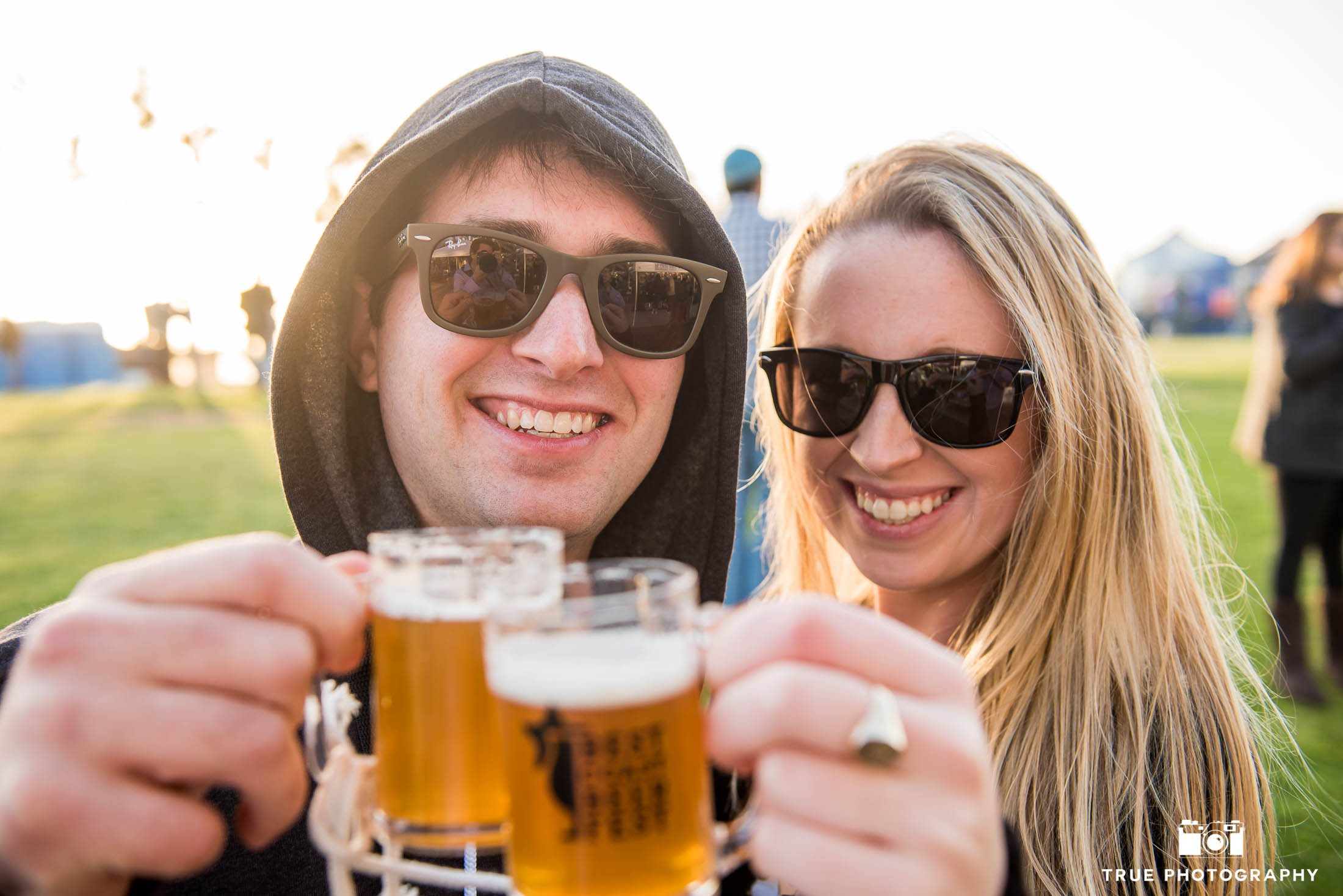 Young couple toasts beer glasses at Best Coast Beer Fest