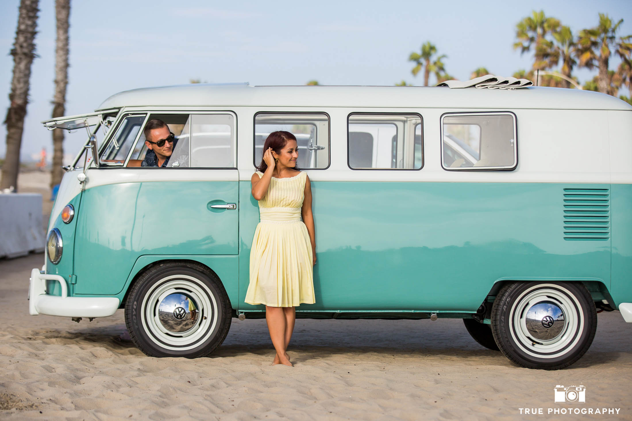 Bride-to-be stands outside vintage Volkswagen bus while Groom-to-be looks at her and drives on beach