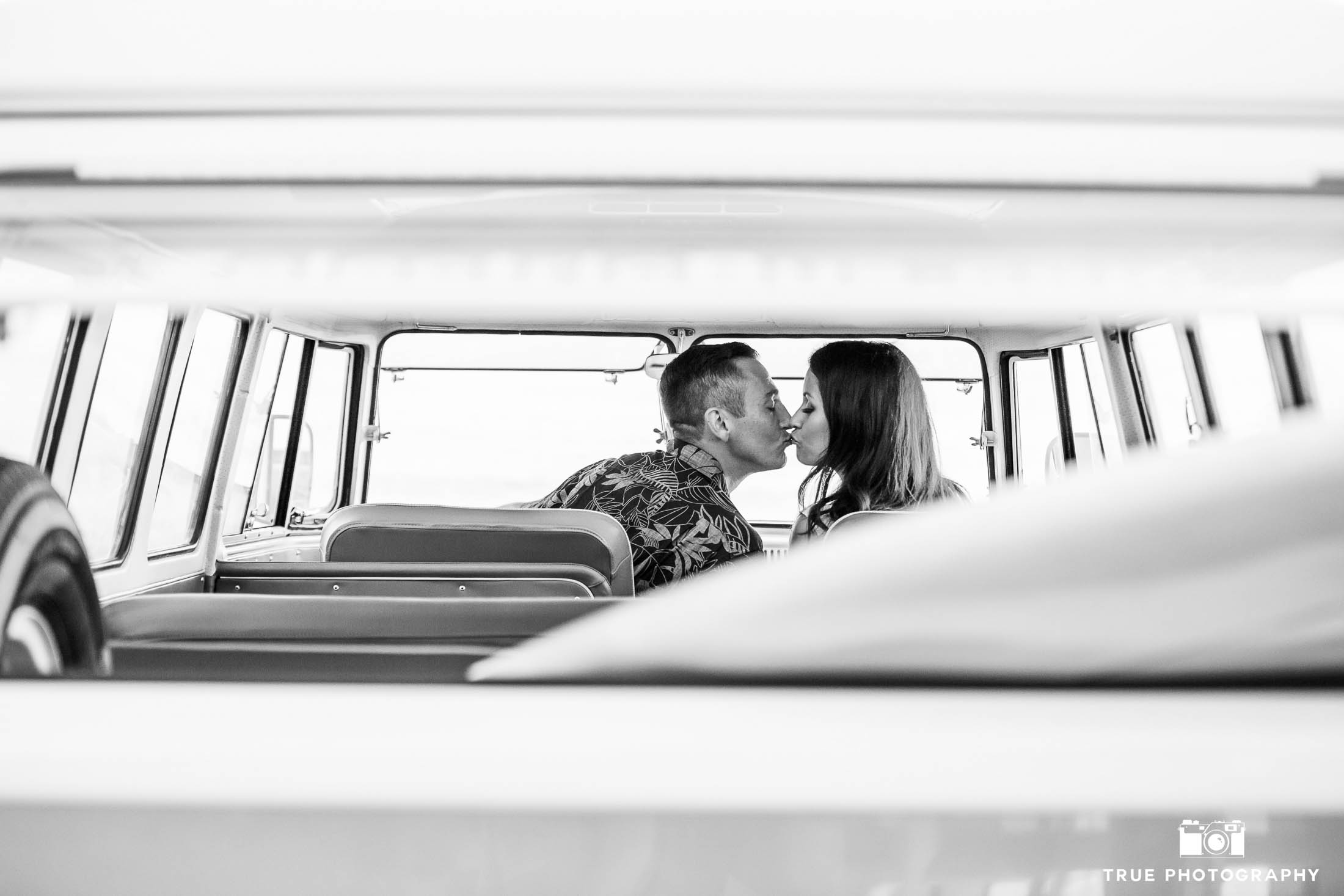 Engaged couple kiss in front seat of volkswagen bus