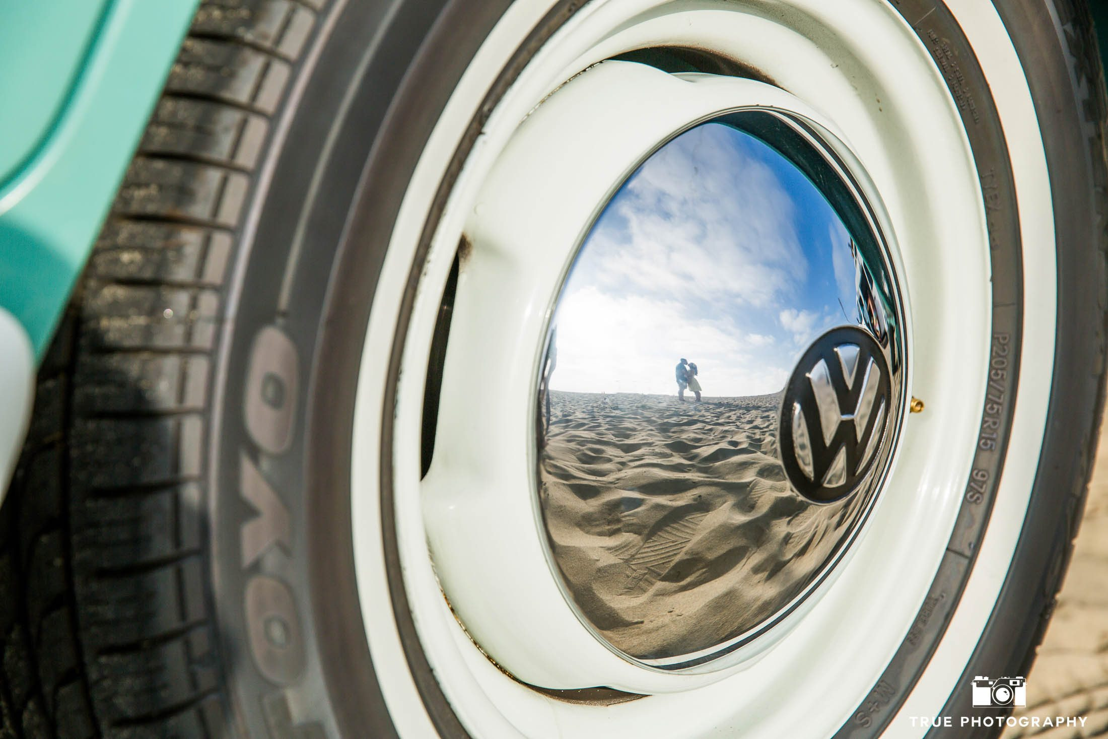 Reflection of engaged couple kissing in metal hubcap of volkswagen bus