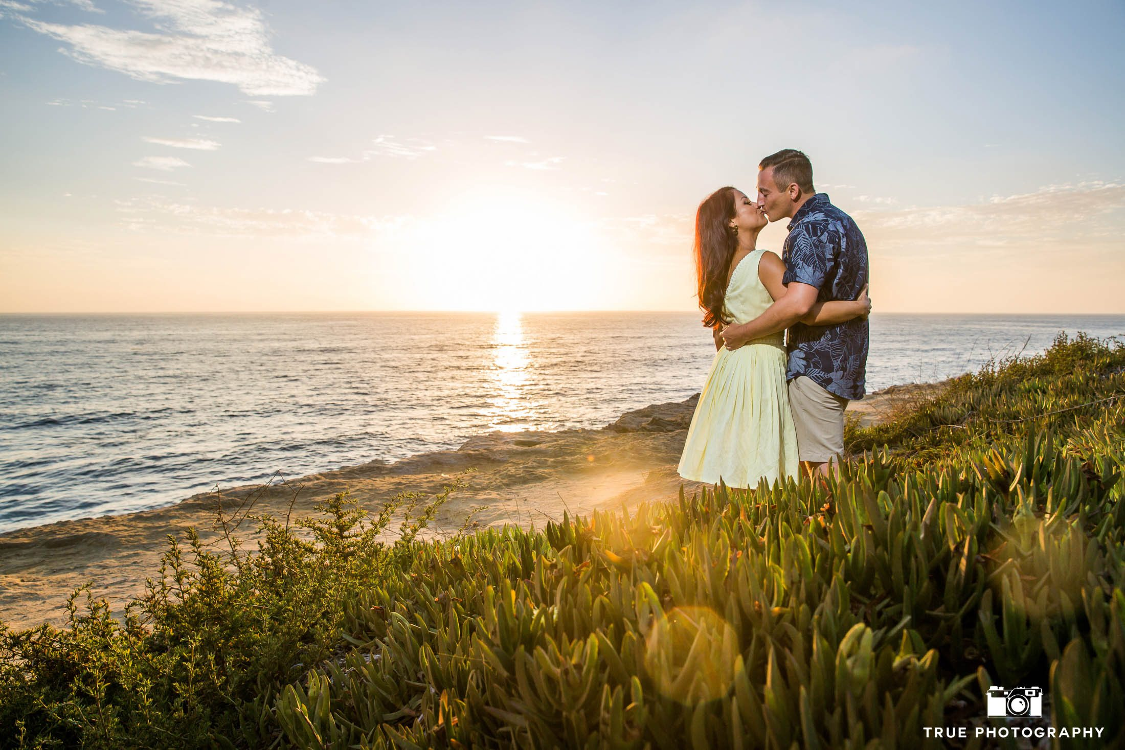 Engaged couple embrace and kiss one another during sunset at Sunset Cliffs