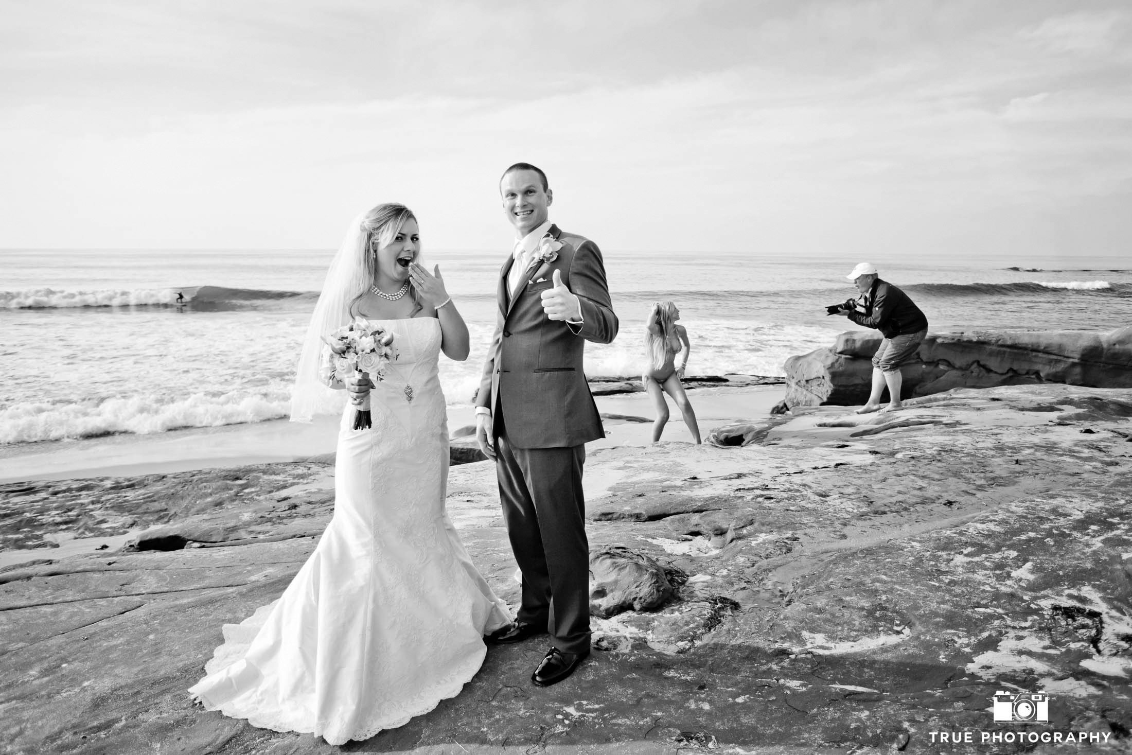 Bride and Groom make funny faces at beach as photographer take photos of model in background