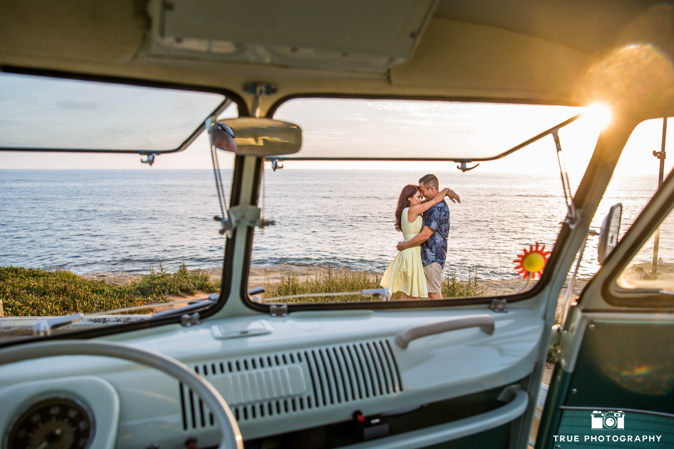 Unique photo of engaged couple embracing during sunset through window of vintage Volkswagen bus during beach engagement session
