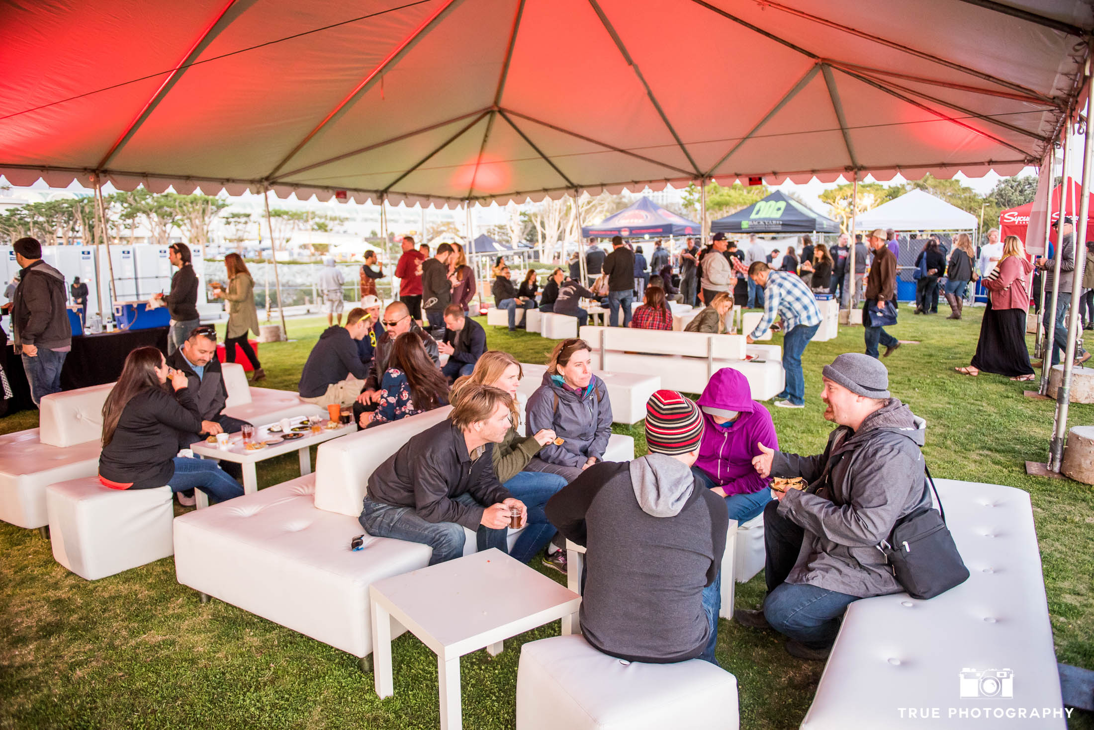 Eventgoers sit and talk under tented lounge during Best Coast Beer Fest