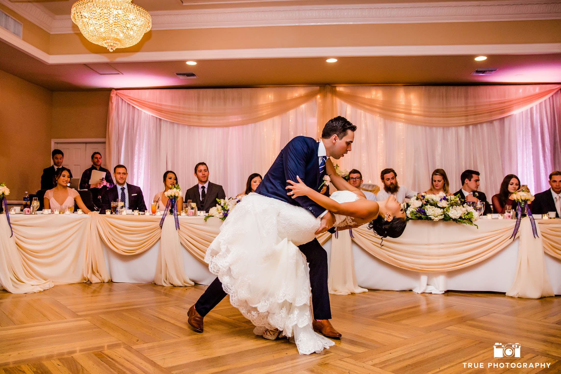 Groom dips his bride for their first dance