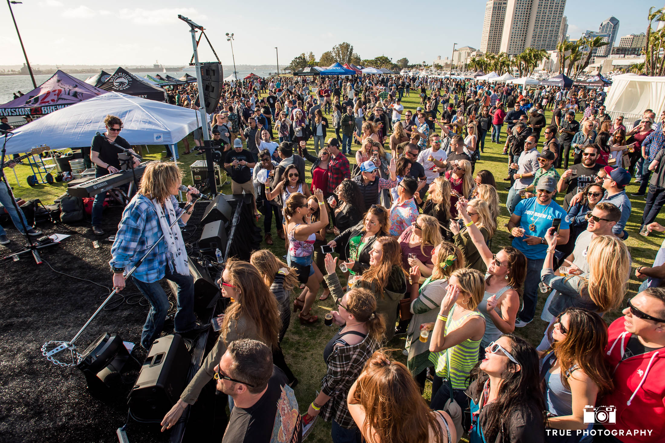 Live band performs for crowd on lawn of Embarcadero Park during beer festival