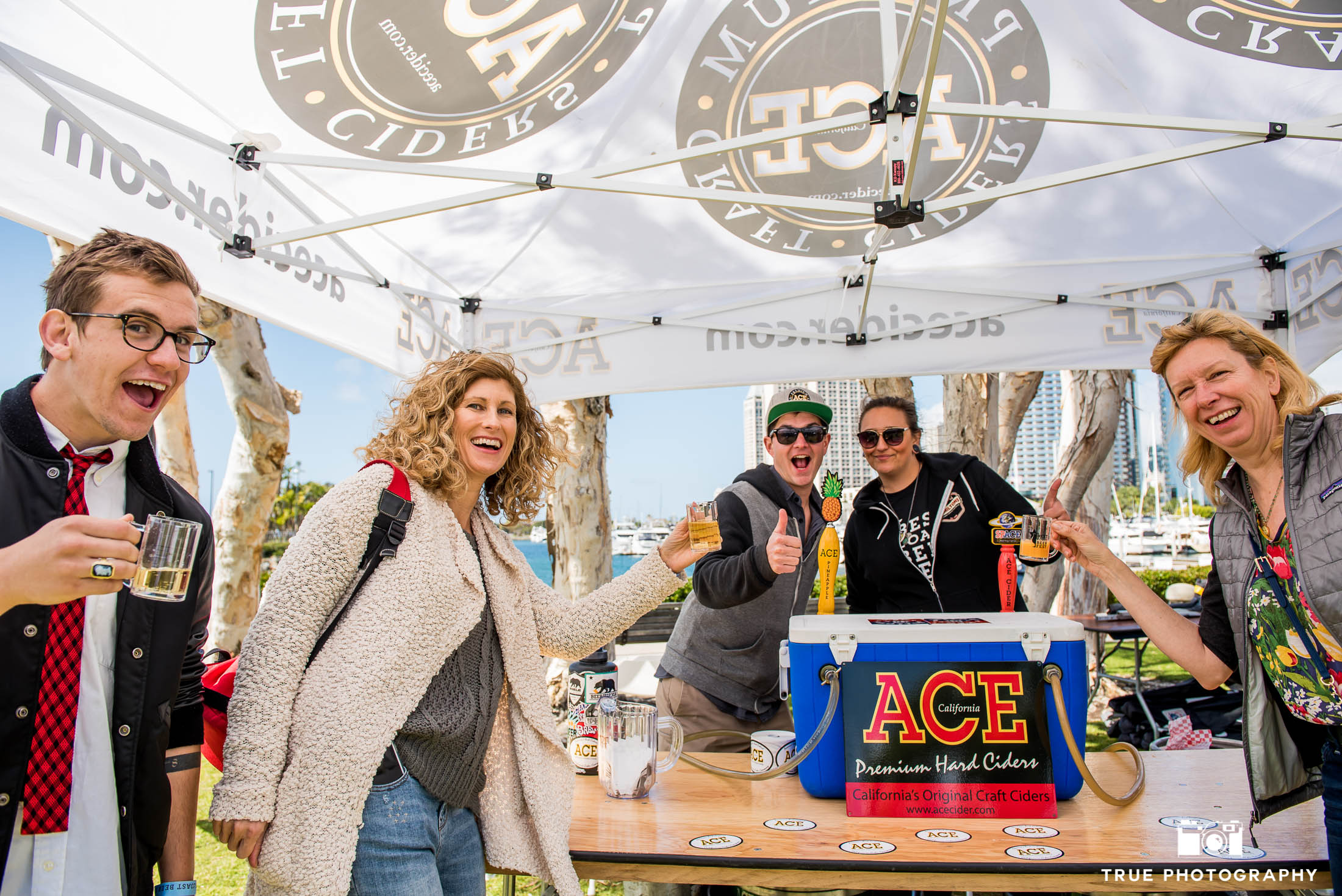 Event goers pose for group photo at ACE Cider Booth during Best Coast Beer Fest