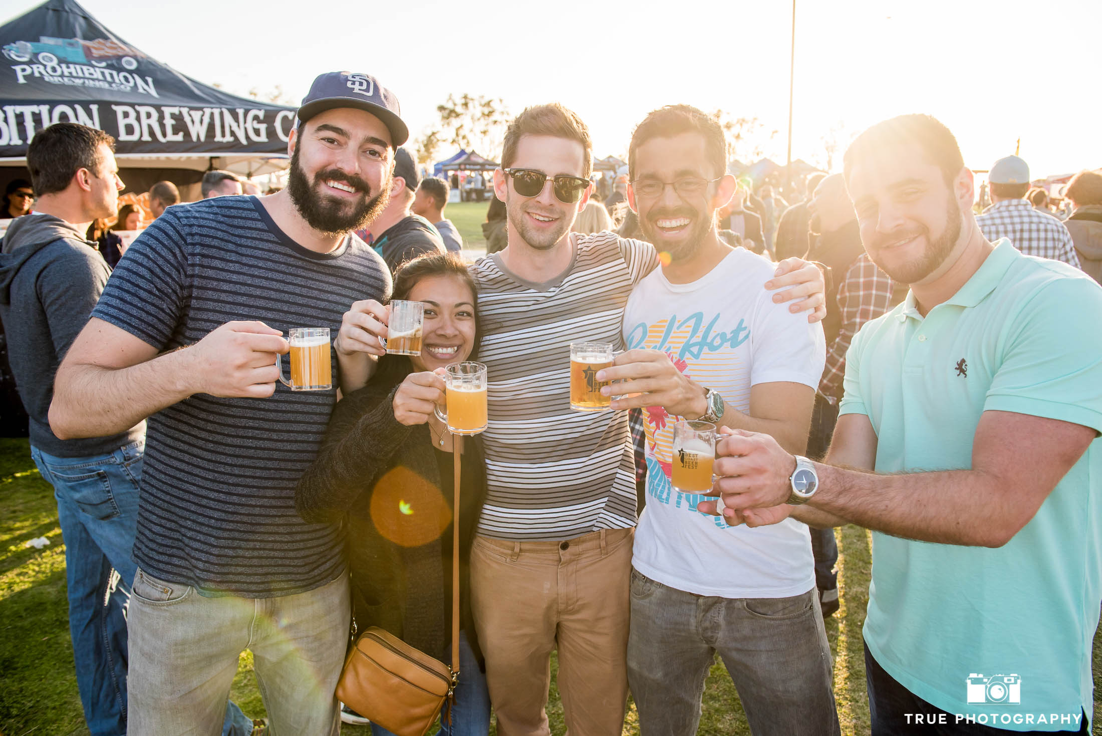 Friends hug and toast with beer tasters during cancer charity event, Best Coast Beer Fest