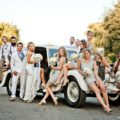 stylish wedding party posing with a vintage rolls royce car