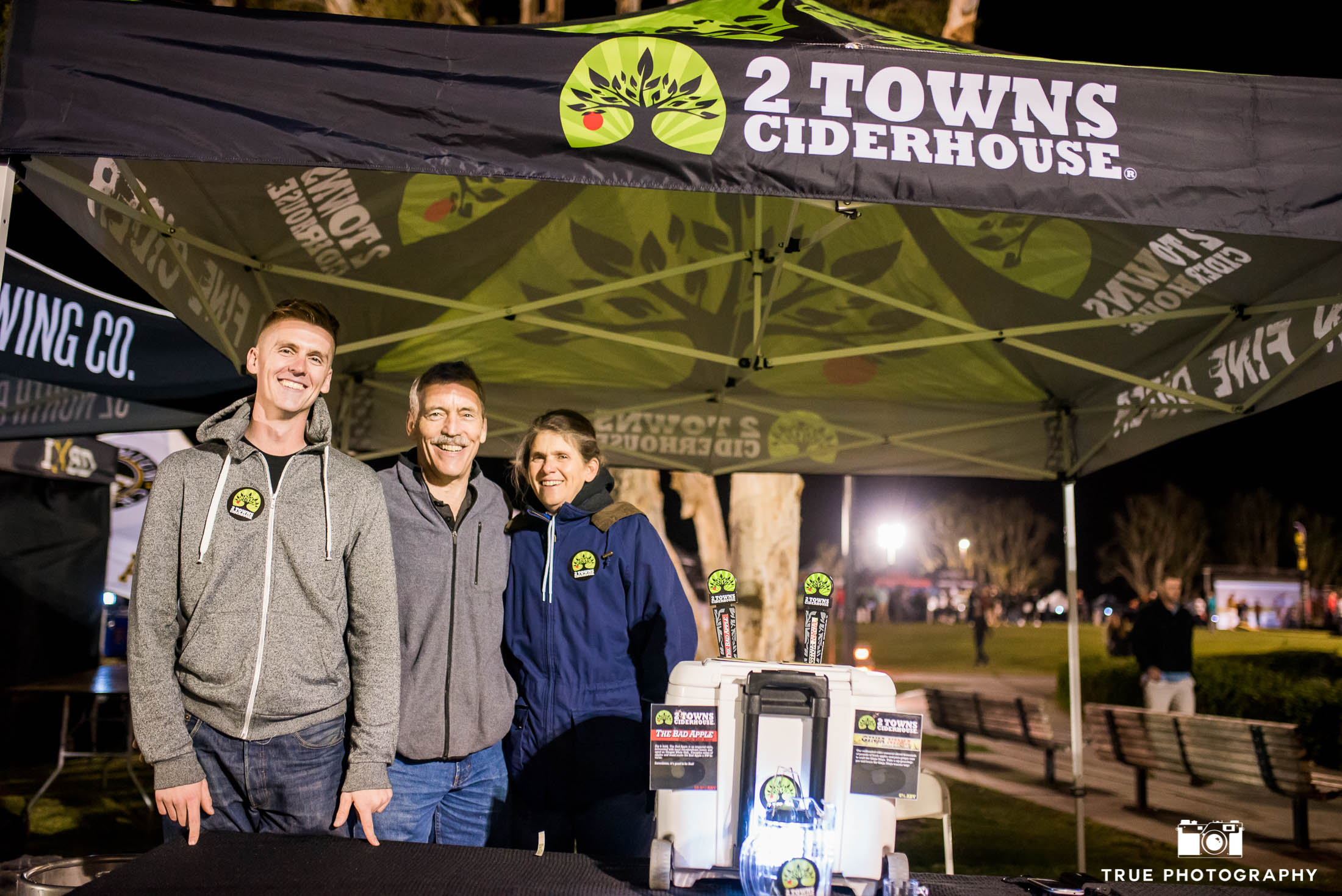 2 Towns Ciderhouse brewers pose for photo at booth during Best Coast Beer Fest