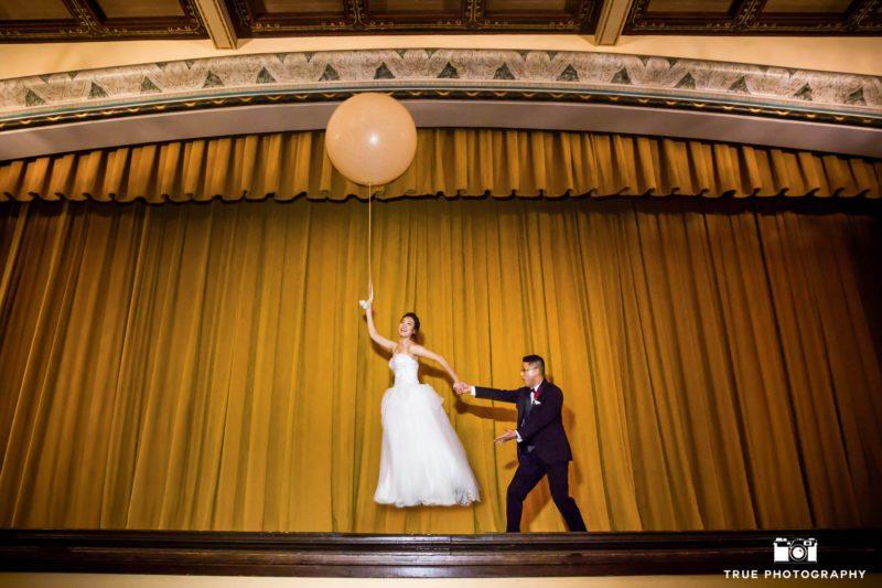 Funny photo of wedding couple with oversized balloon at balboa park