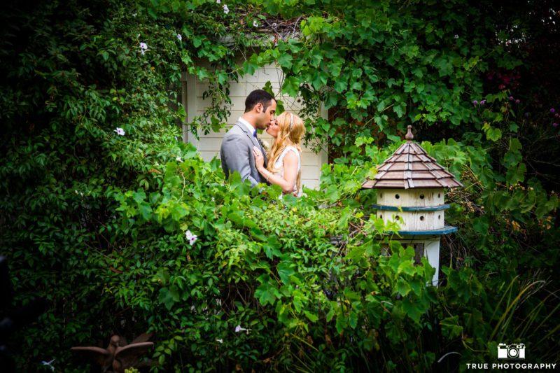 Bride and groom explore a romantic garden.