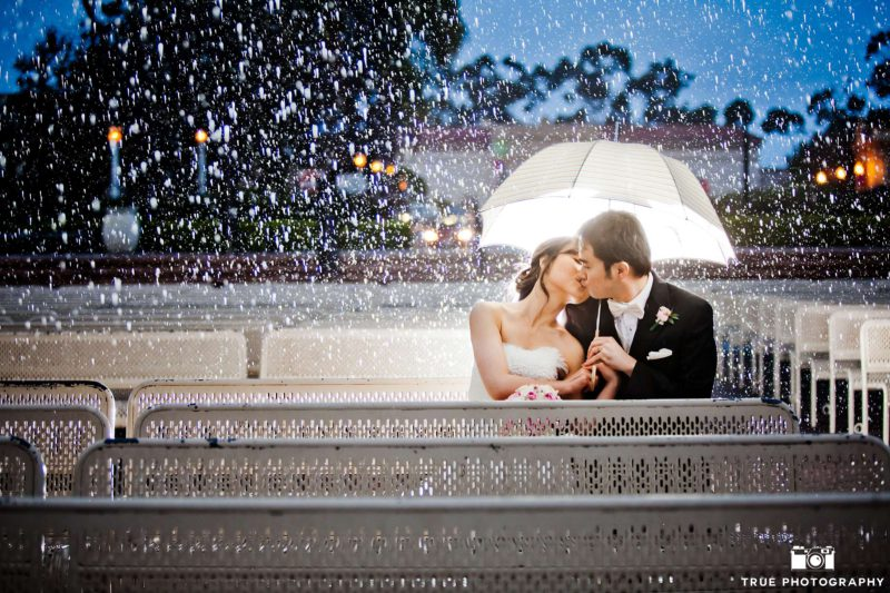 A bride and groom kissing in the organ pavilion on a rainy day.