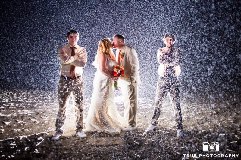 Two groomsmen stand guard in rain as newlyweds kiss.