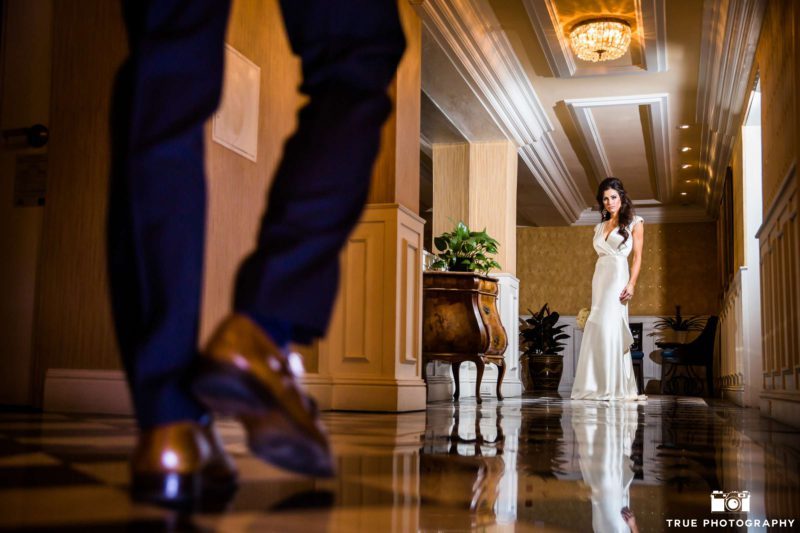 A couple walks down the hall to meet each other.